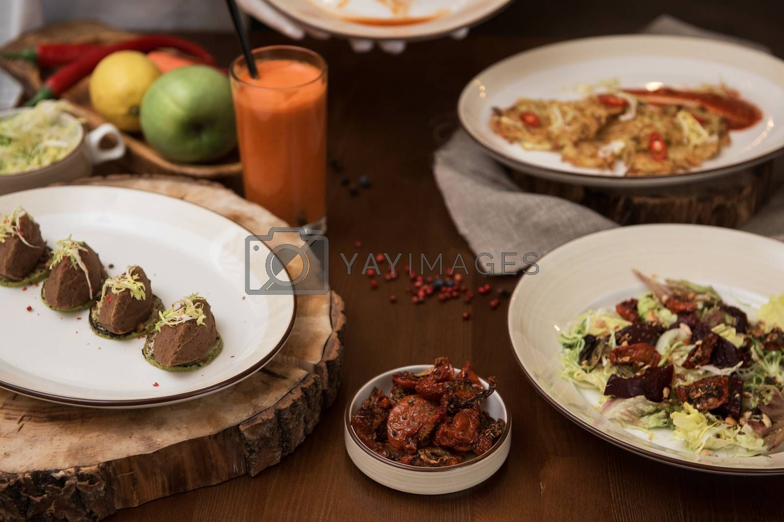 Healthy vegeterian food on brown wood board. Spring vitamin dieting food. Salad from beet with dried tomatoes and cabbage, potato vegan pancakes, dried tomatoes, pate from red beans, baked vegetables in layers, fruits and carrot juice