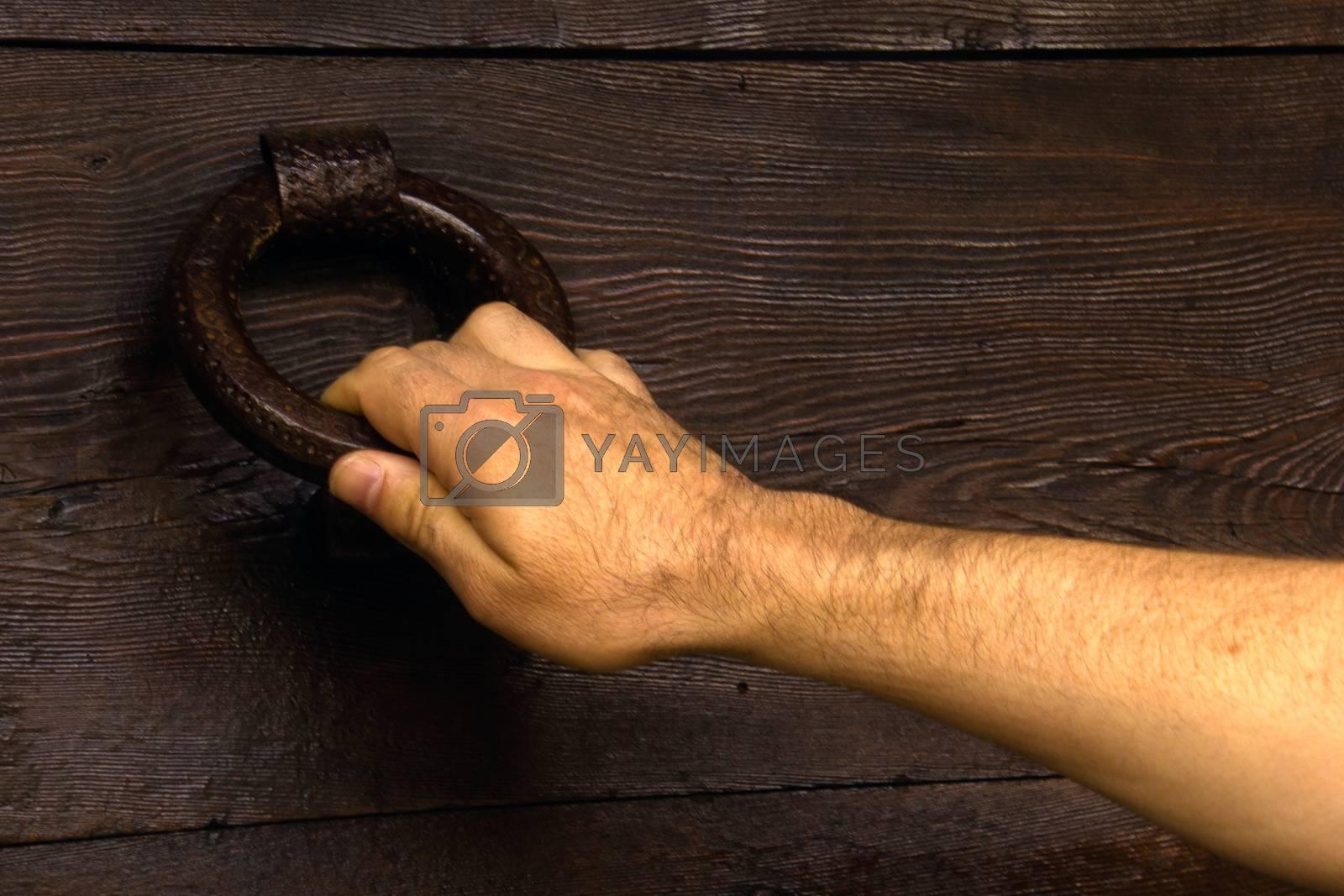 man's hand holding a door's knocker