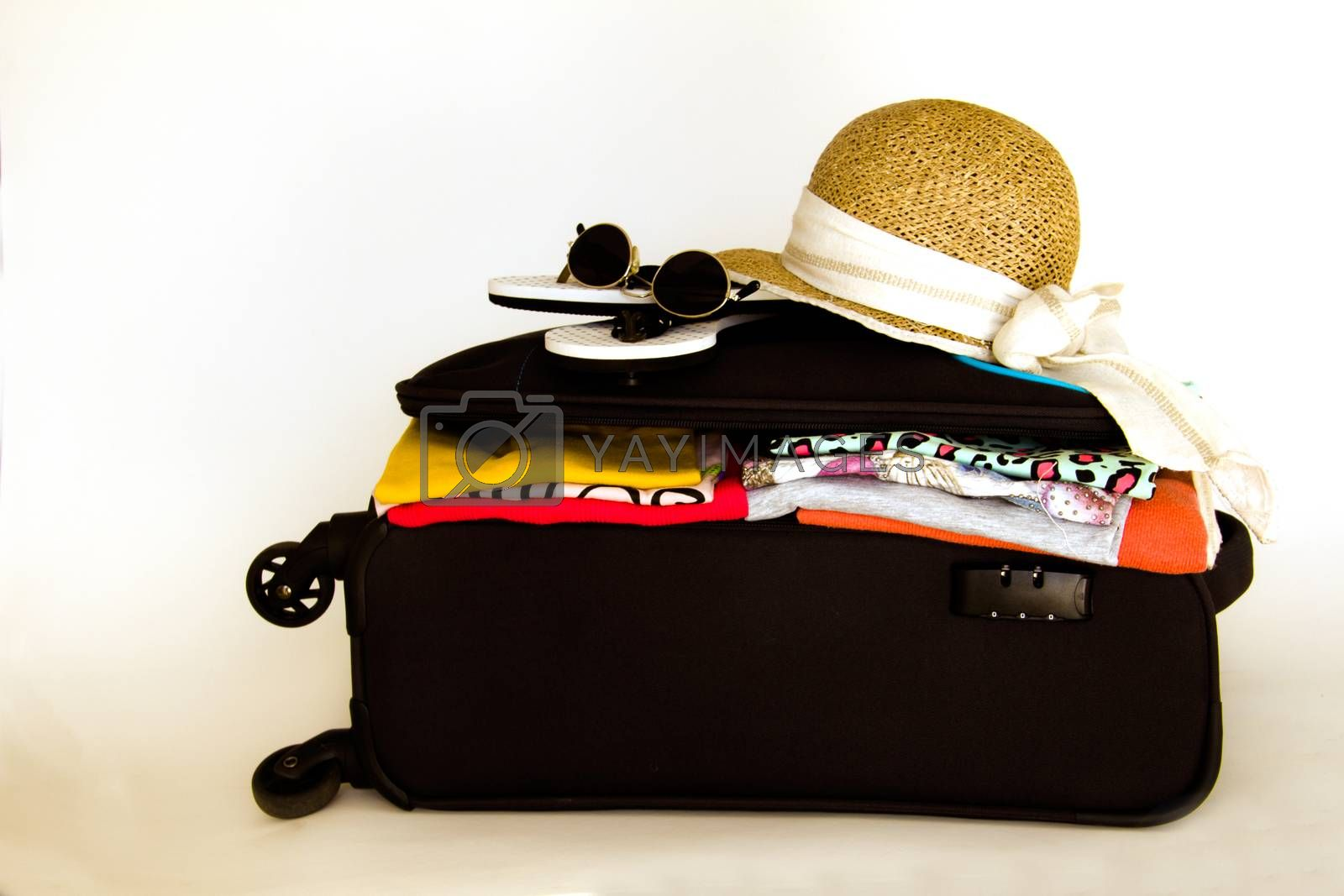 opened suitcase containing clothes with sunglasses and a hat on the top