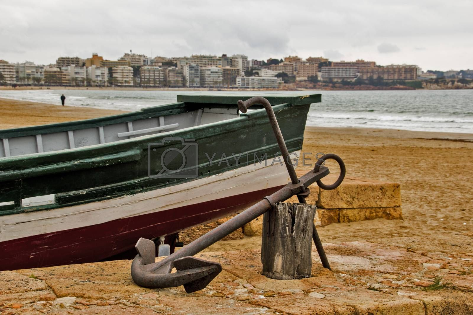 Fishing boat anchored in the sand in Salou, Catalonia, at the seaside and a buildings background