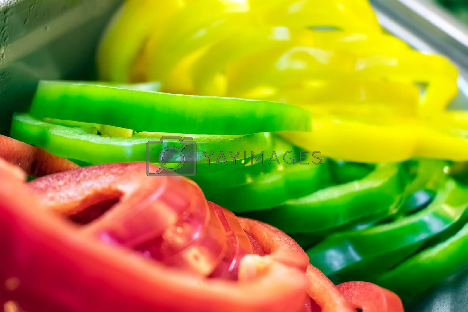 Freshly Sliced Yellow, Green and Red Bell Pepper in a Salad Bar