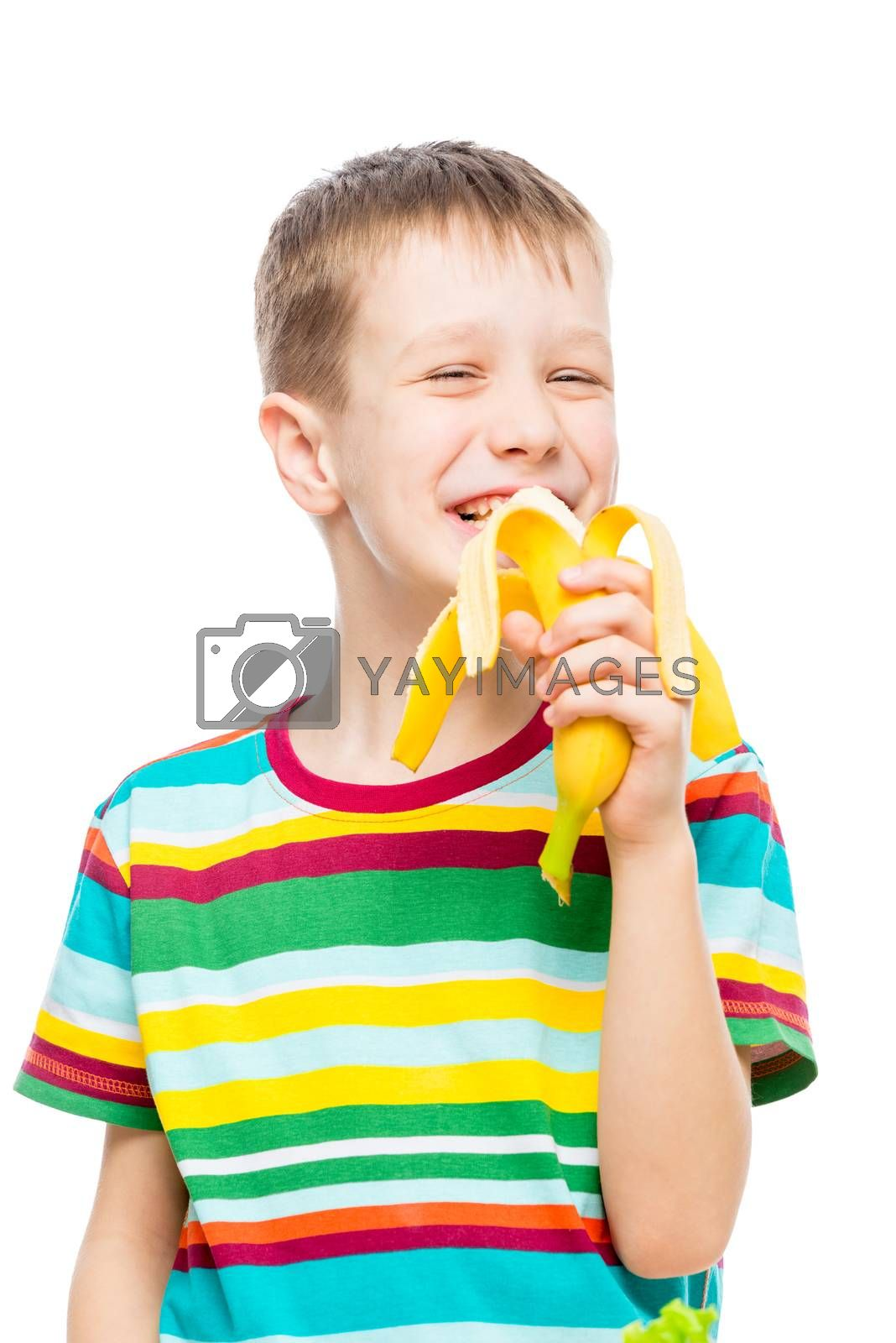 vertical portrait of a boy who eats a tasty banana on a white background, portrait is isolated