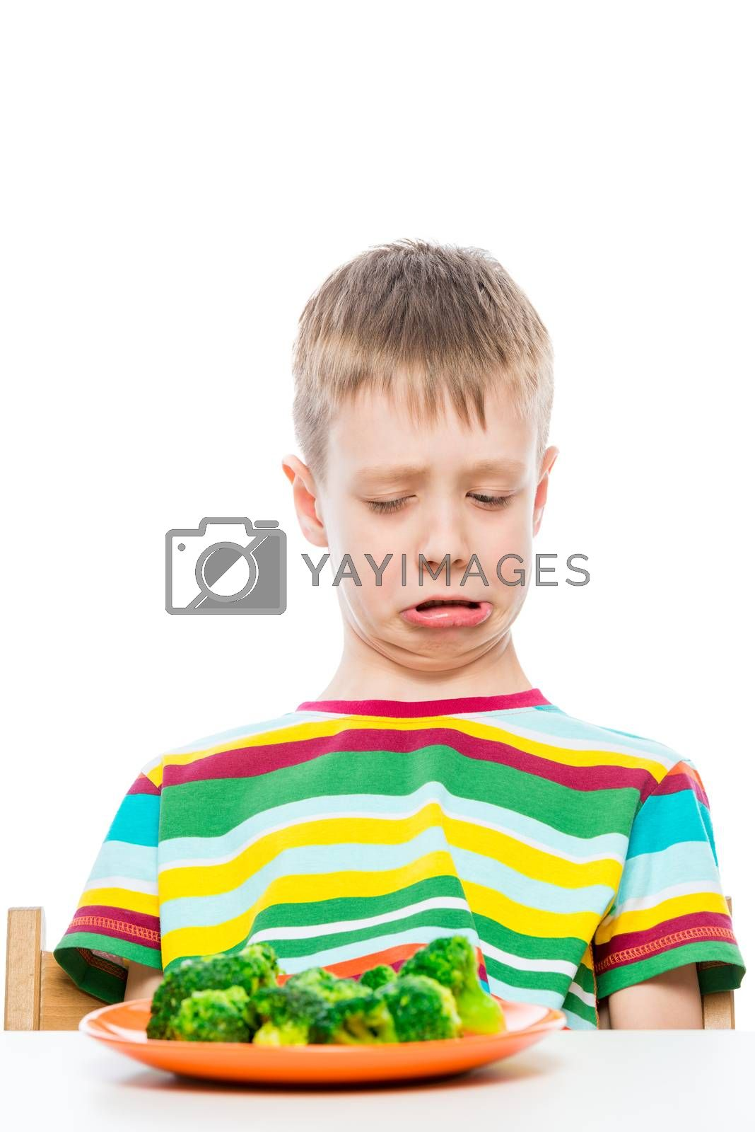 boy with disgust looks at a plate of broccoli, portrait on white background isolated