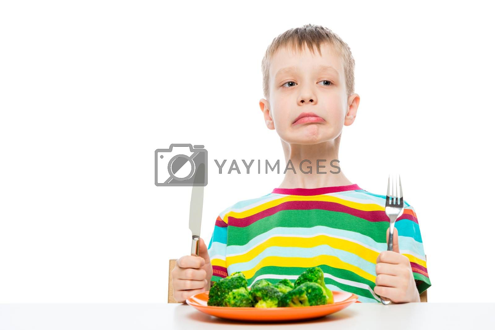 Boy disgusted with eating broccoli, portrait isolated on white background