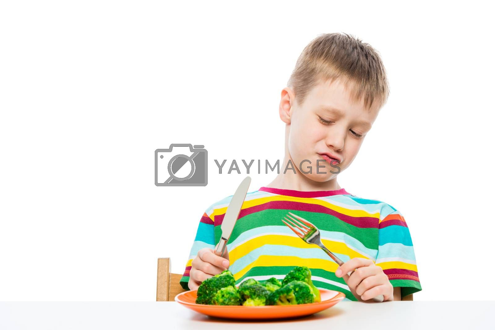 A boy of 10 years old looks at broccoli in a plate in disgust, portrait is isolated on a white background
