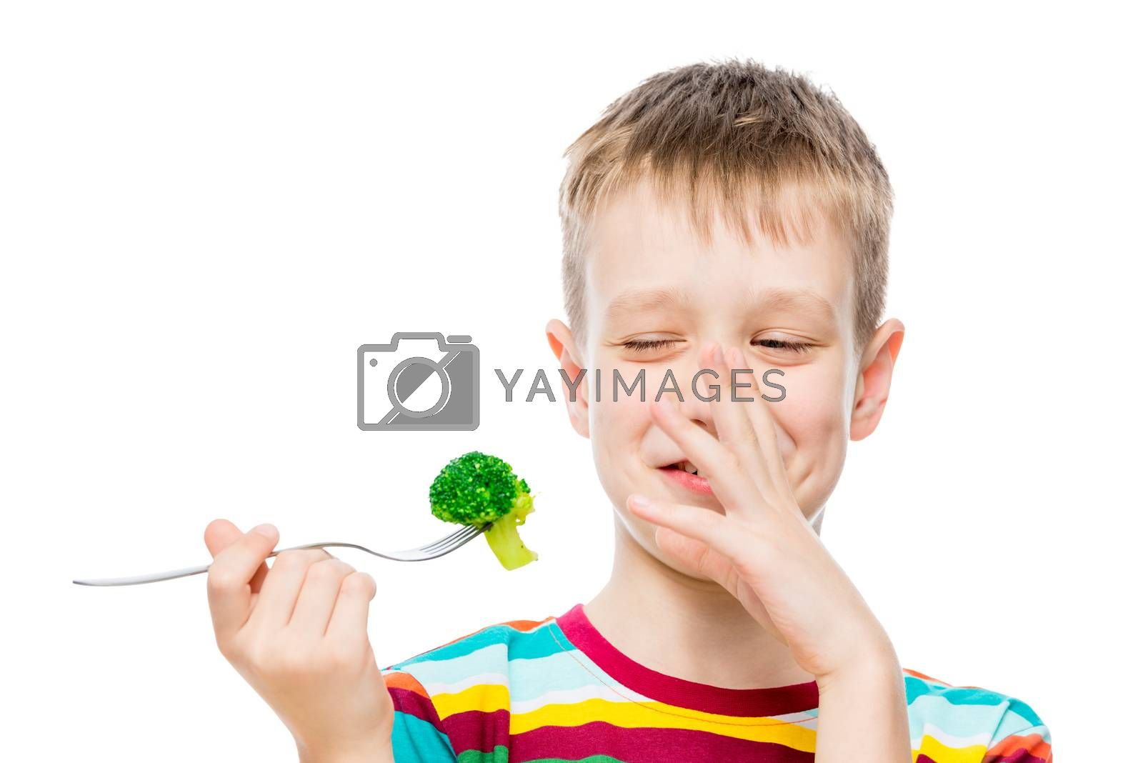 The boy with contempt looks at broccoli, portrait is isolated on white background