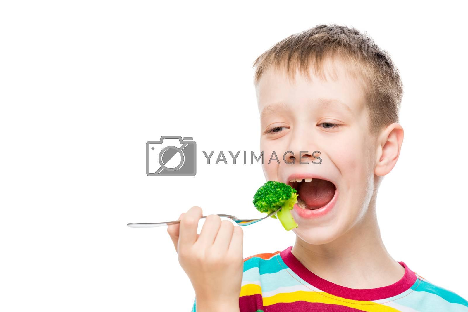Portrait of a boy on a white background, the child eats broccoli