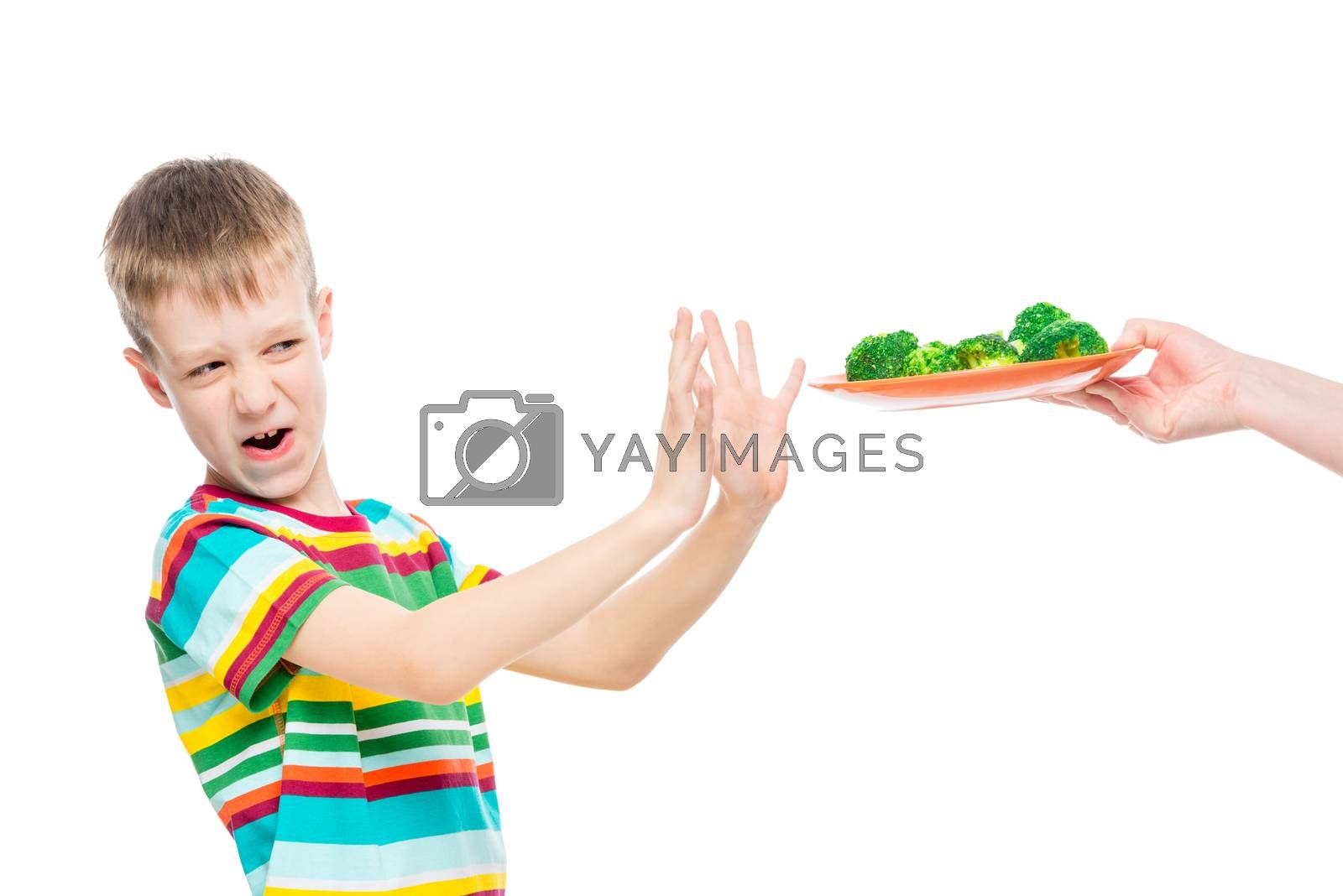 Boy refuses plate of broccoli for lunch, portrait is isolated on white background