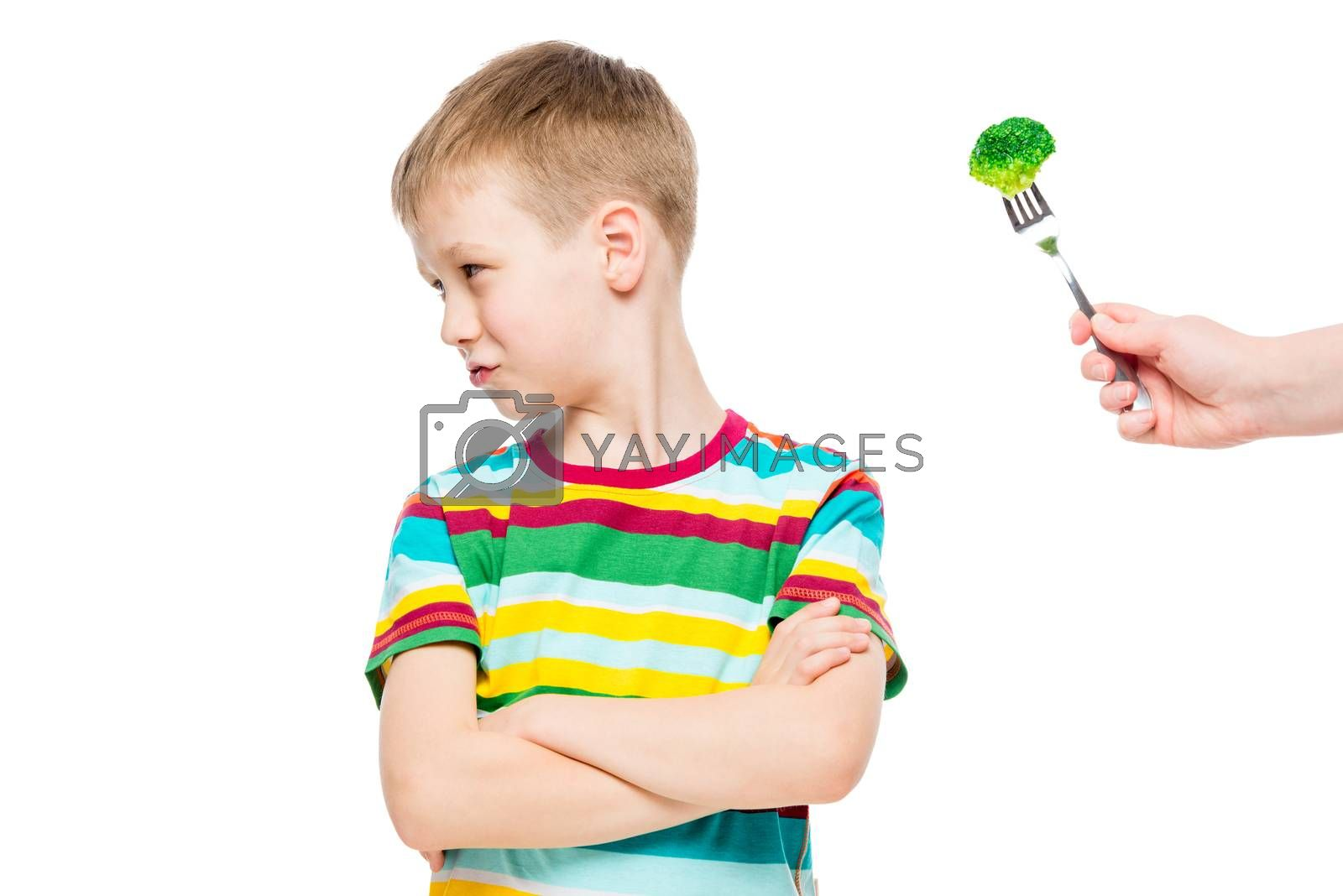 Offended displeased boy refuses serving of healthy broccoli, portrait is isolated