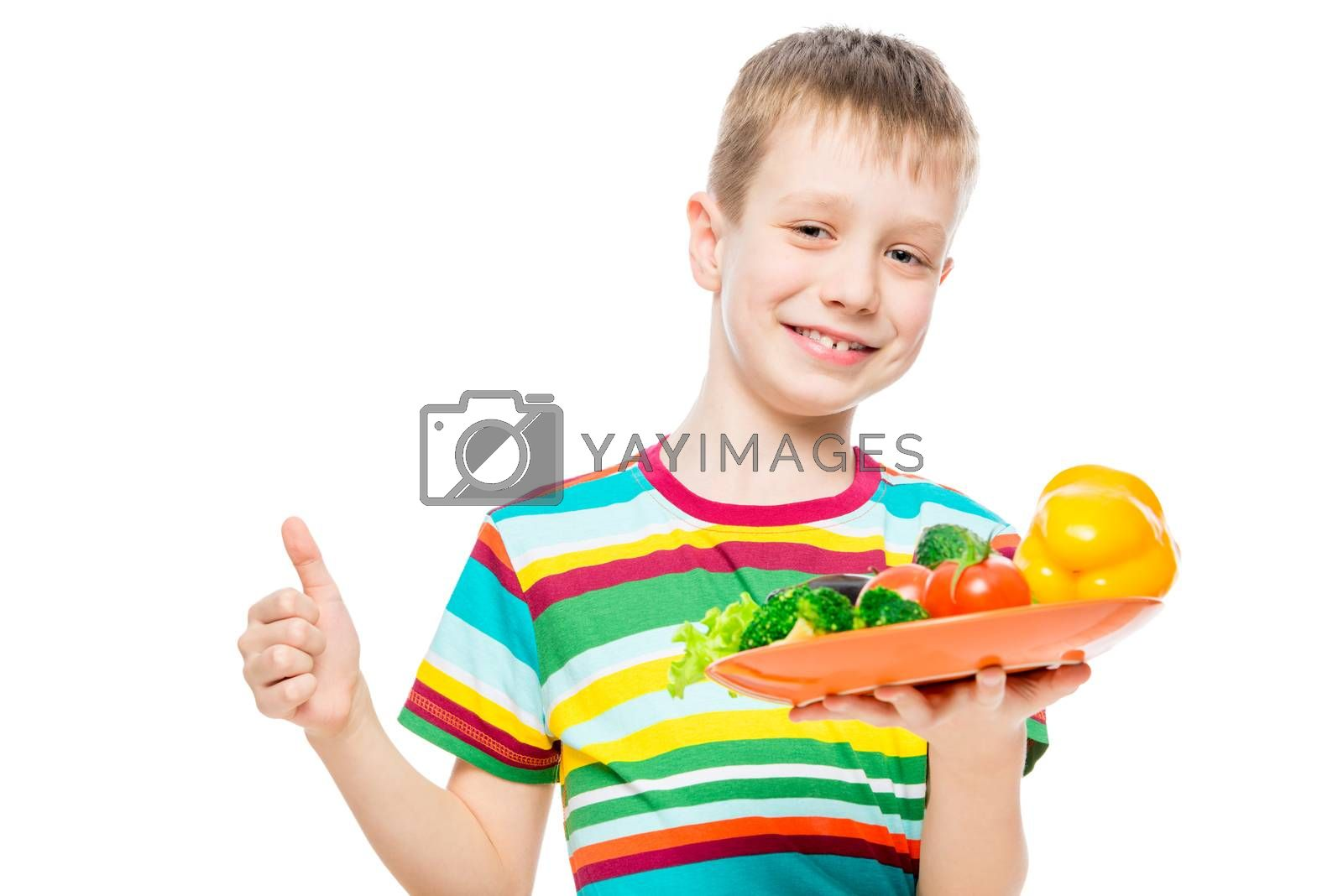 satisfied boy with a plate of healthy vegetables isolated on white background portrait