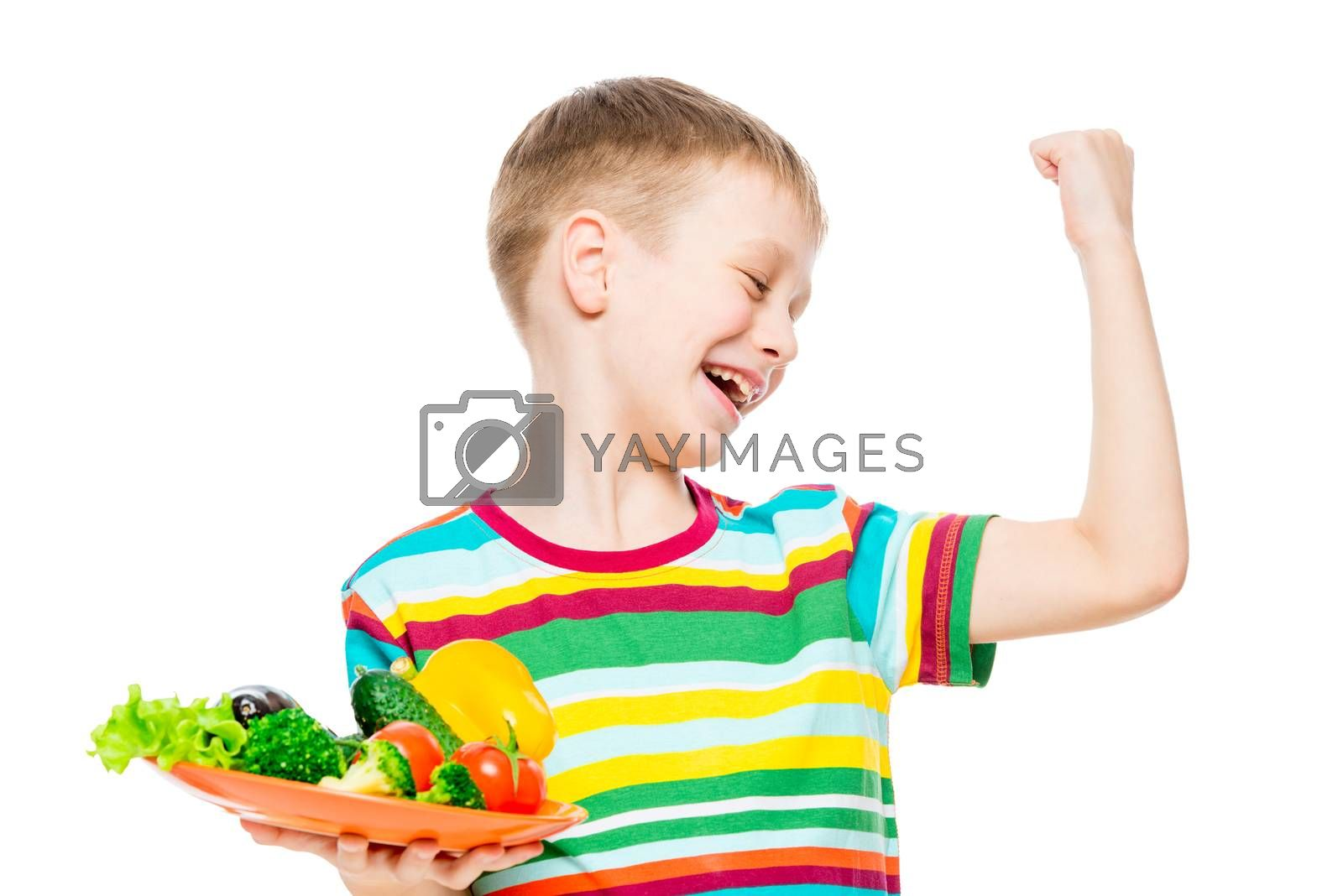 a boy with a plate of fresh vegetables shows his muscles from wholesome food, the portrait is isolated