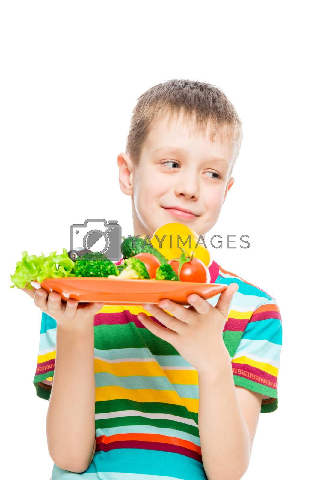 vertical portrait of a boy with a plate of vegetables on white background isolated