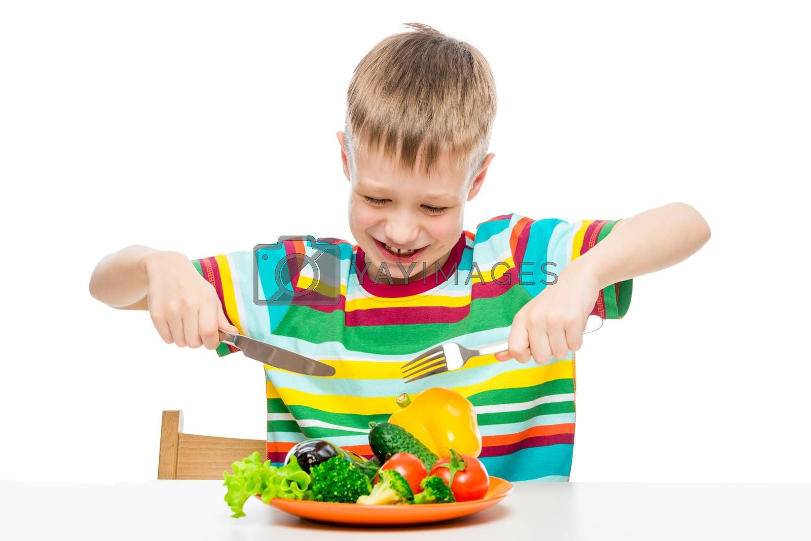 hungry boy 10 years old with a plate of vegetables, concept photo diet and healthy food