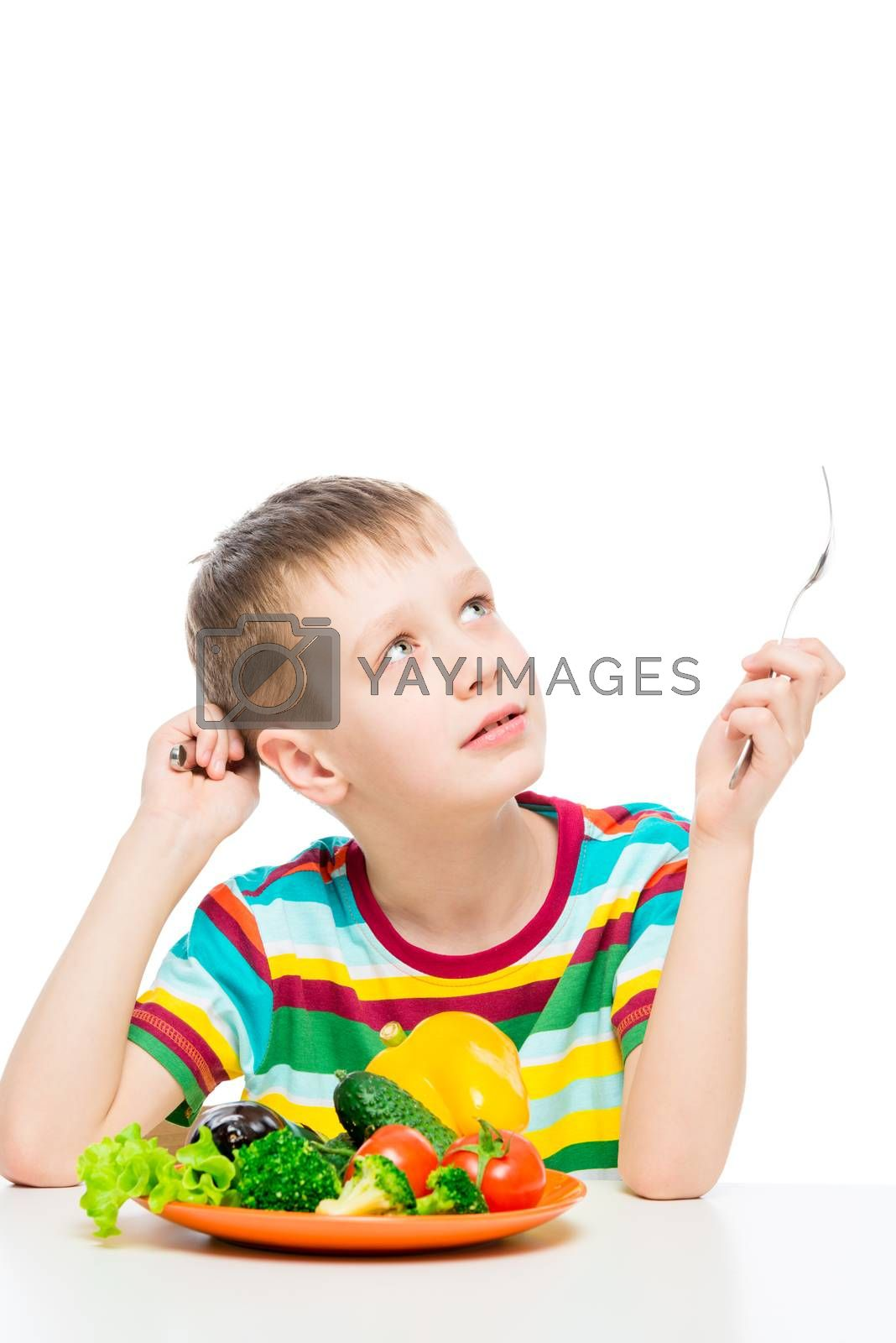 portrait of a boy at the table with a plate of vegetables for lunch, isolated on white background