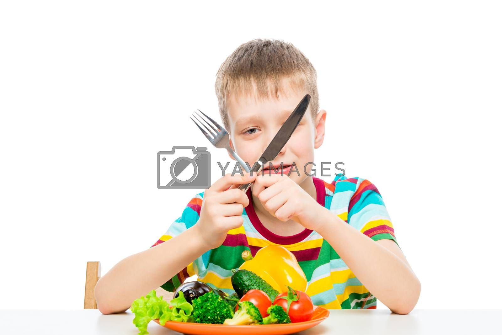 boy with a knife and fork eating fresh raw vegetables, portrait isolated