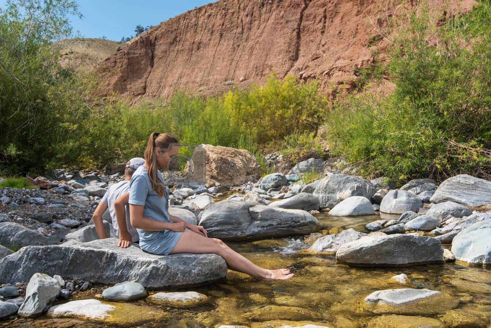 Woman with her son have rest on mountain river in Altai mountain, beauty summer landcape