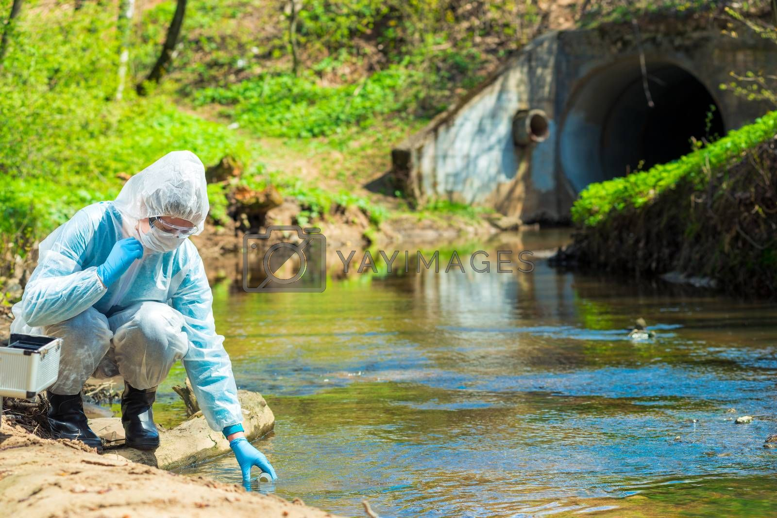 Scientist in protective suite taking water samples from the river