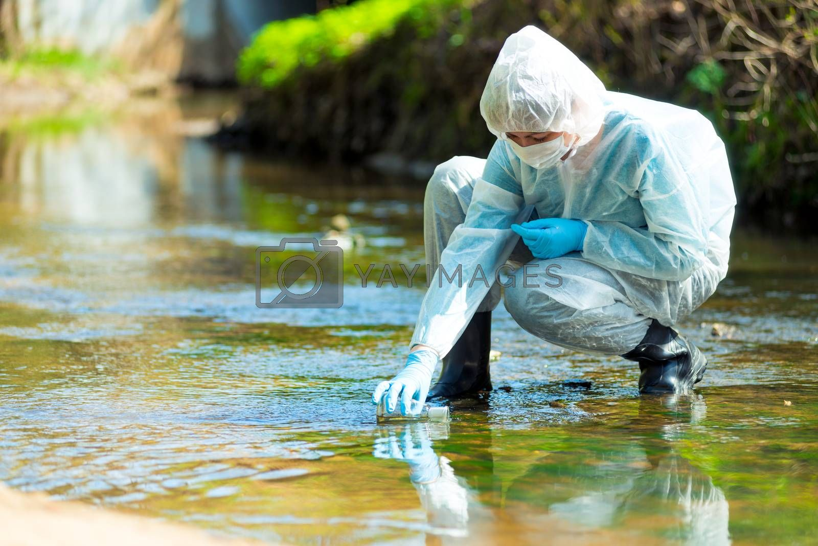 scientist researcher in protective suit takes water for analysis from polluted river