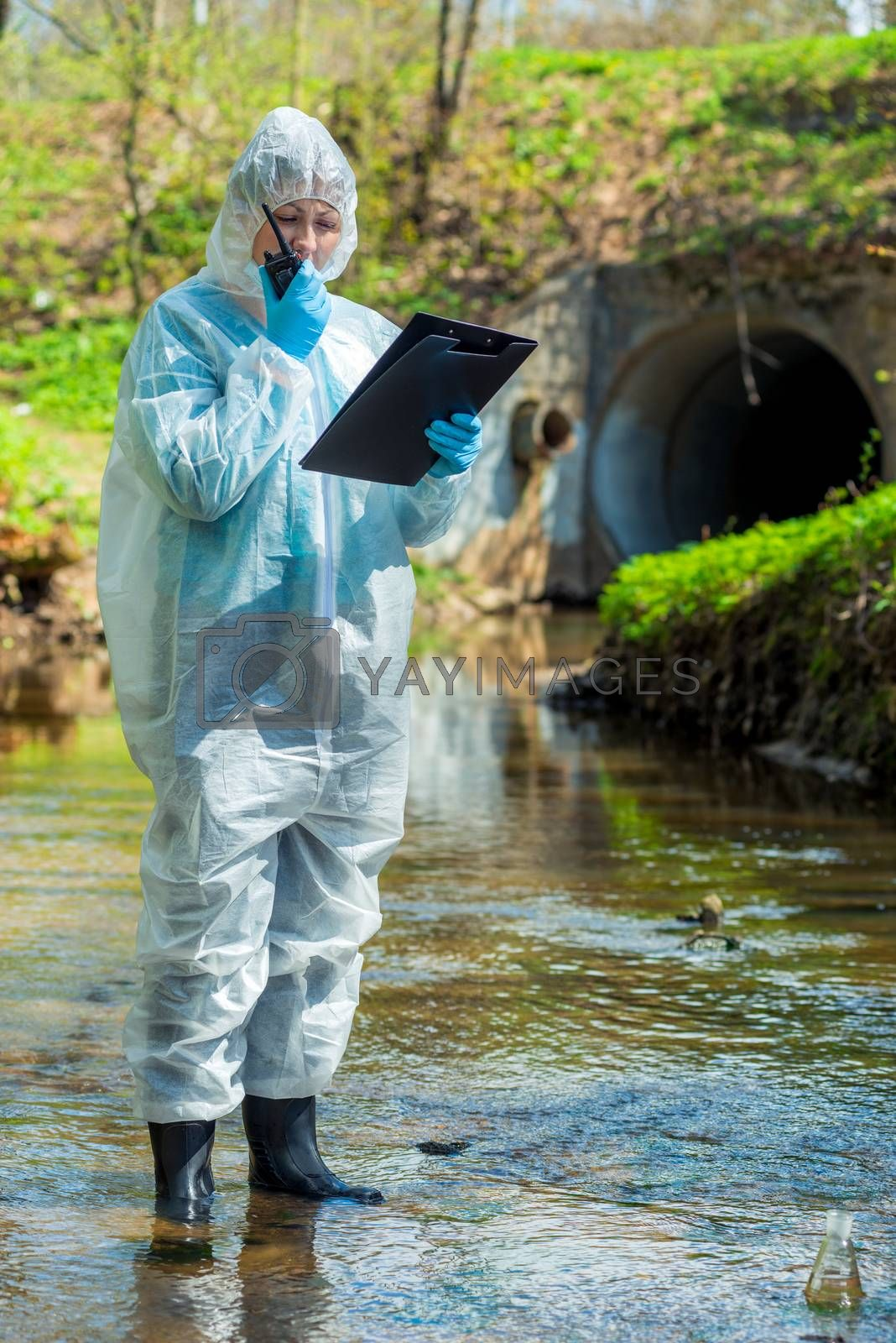 environmental scientist with a walkie-talkie and a notebook on the background of a sewer pipe