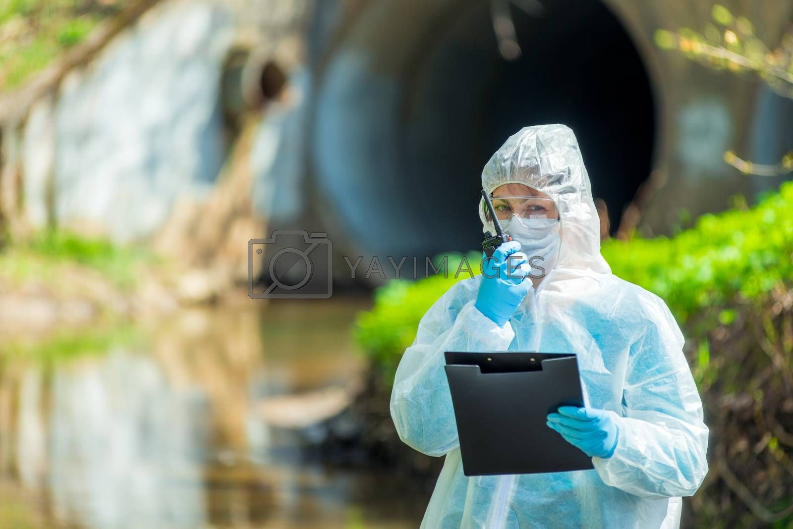 horizontal portrait of a scientist next to a sewer pipe with a walkie-talkie in hand