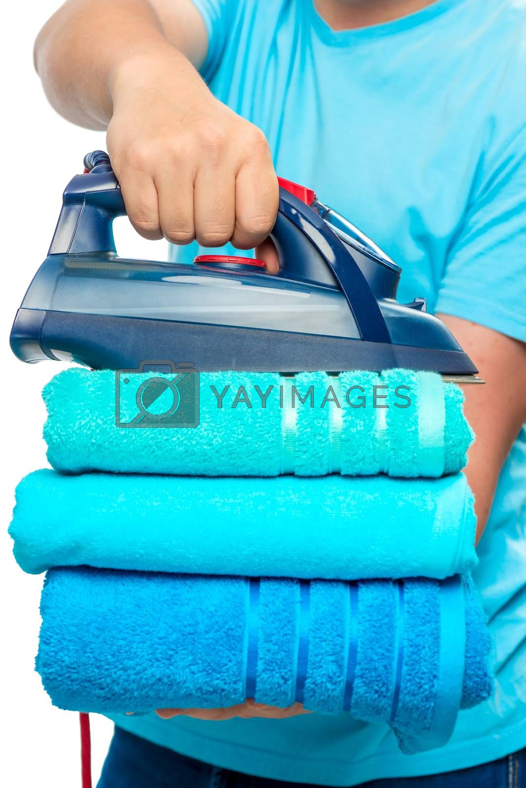 a stack of ironed terry towels and an iron in male hands close-up