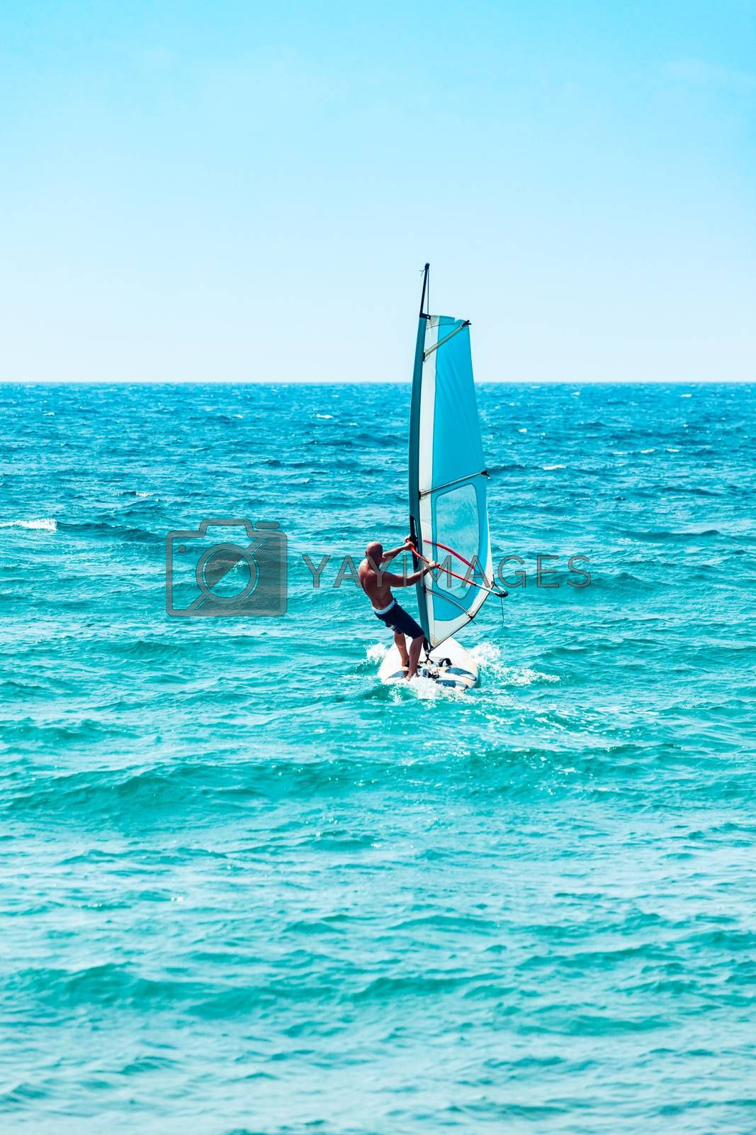 Windsurfer in action, sportive man riding windsurf in the sea, extreme water sport, active summer vacation, happy healthy lifestyle