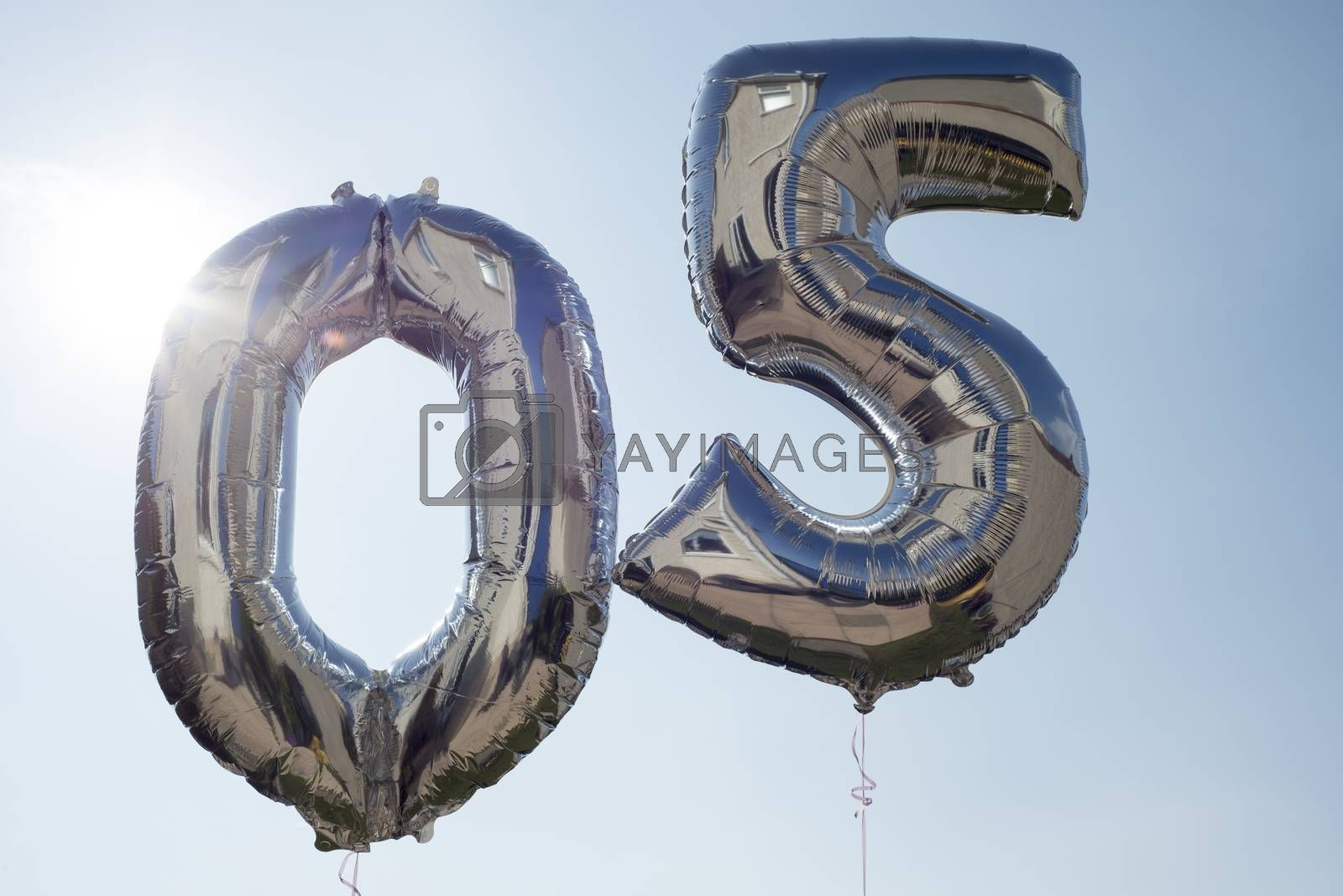 numbers 0 and 5 helium filled balloons against a blue sky