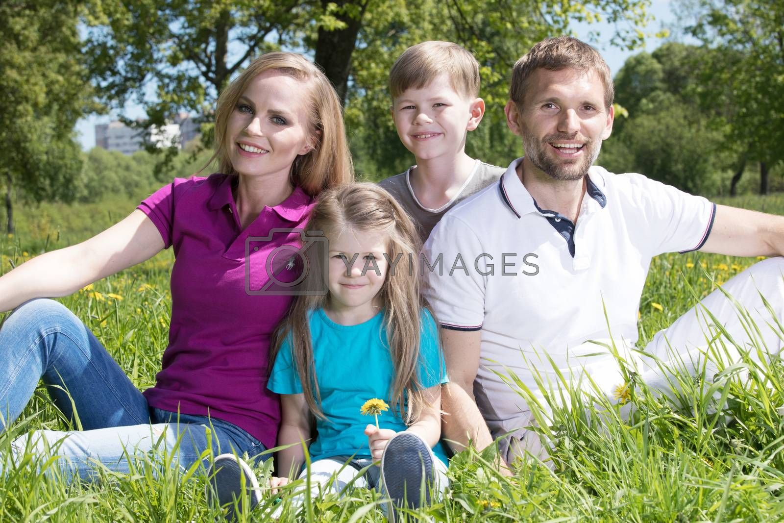 Father, mother and their children are sitting on the green grass in the summer park