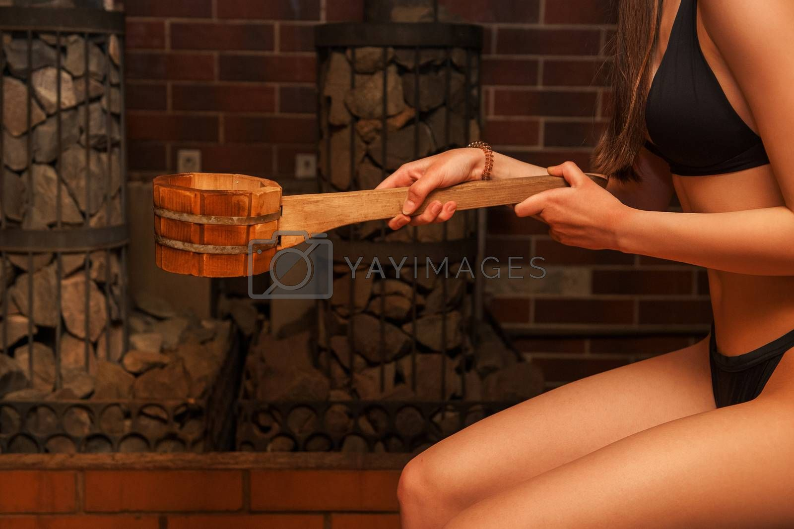 Wooden bath accessories with aromatic oil bottle for bath in the sauna and woman on background
