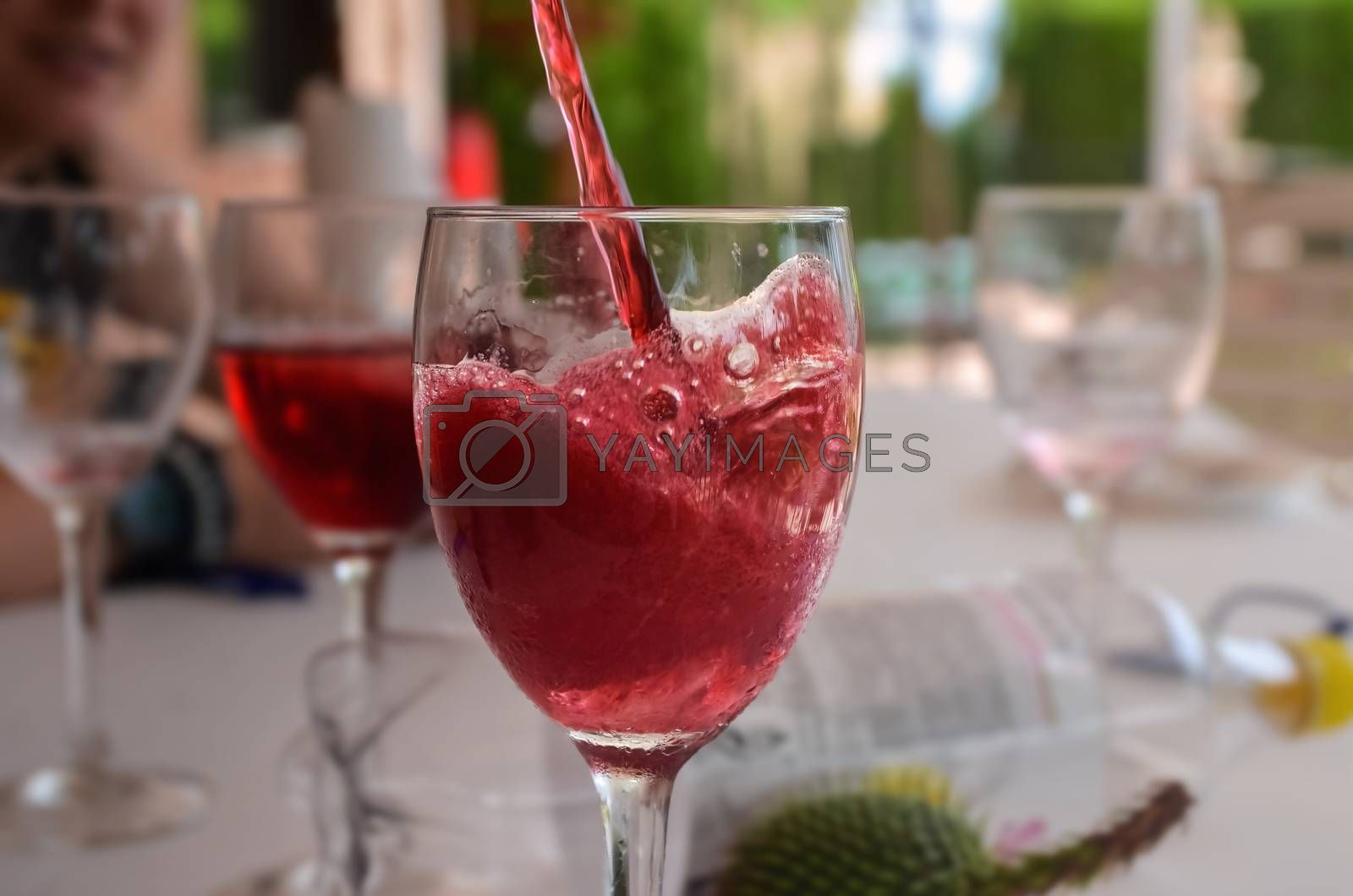Red wine of summer falling in a glass with ice