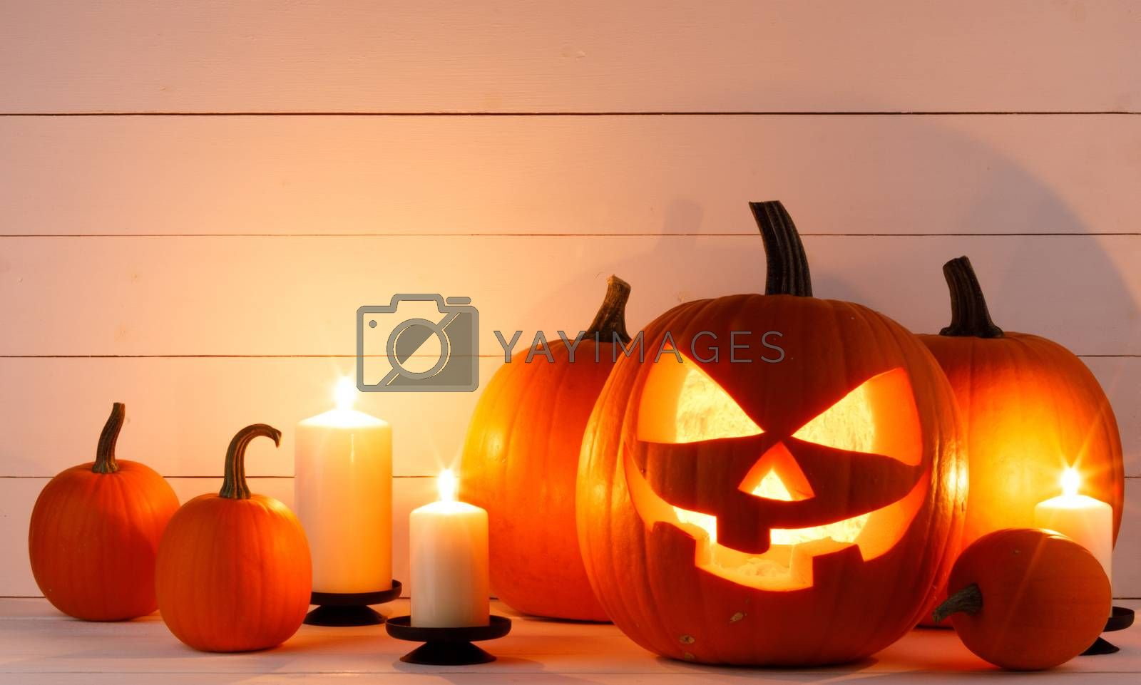 Halloween pumpkin head jack o lantern and candles on wooden background
