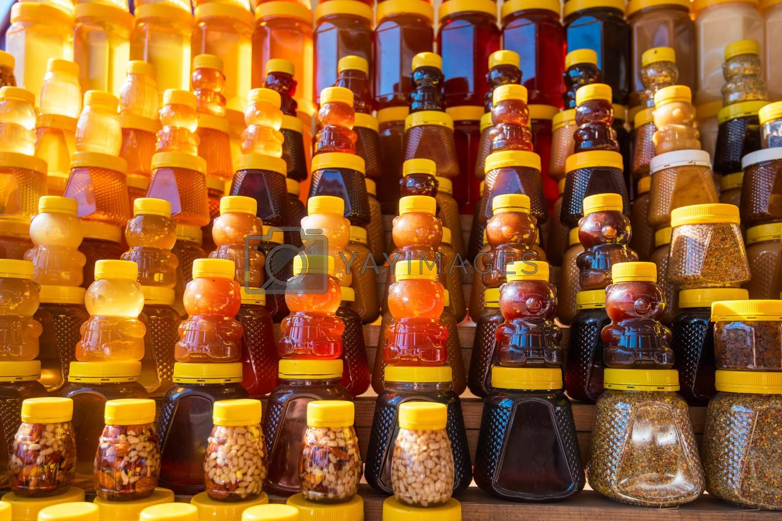 Many jars with fresh organic honey on farm market. Colorful honey with fruit berries and nuts in the jar, on a market in Altai.