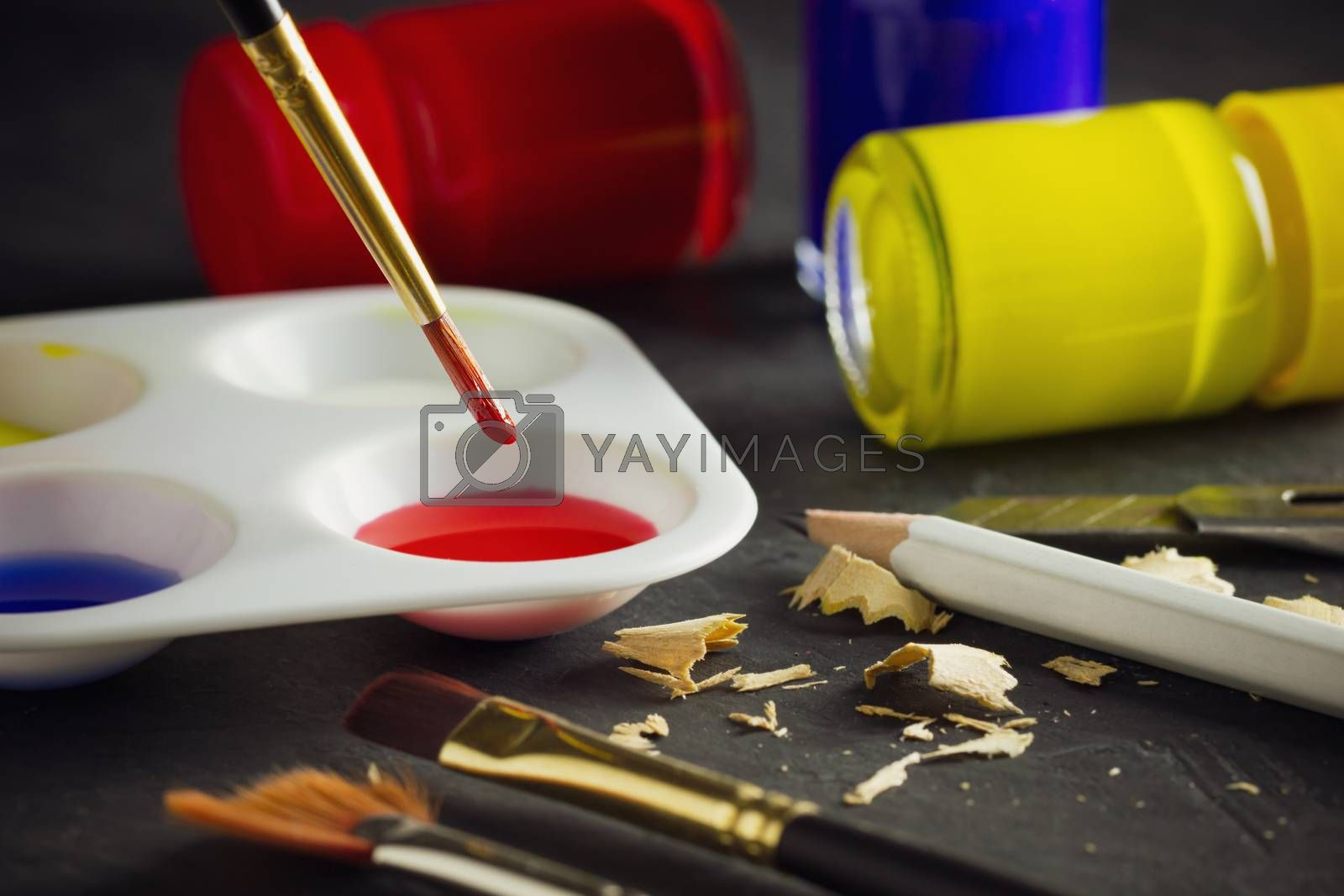 Closeup artist paint brush above color plate and poster color bo by SaitanSainam
