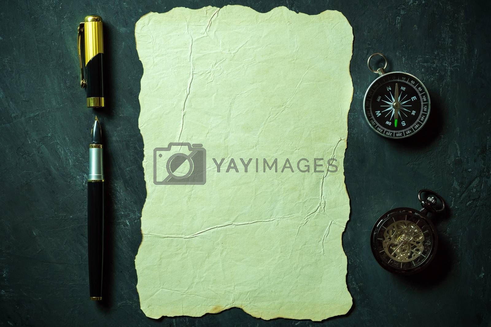 Vintage paper and pen with compass and pocket watch on black bac by SaitanSainam