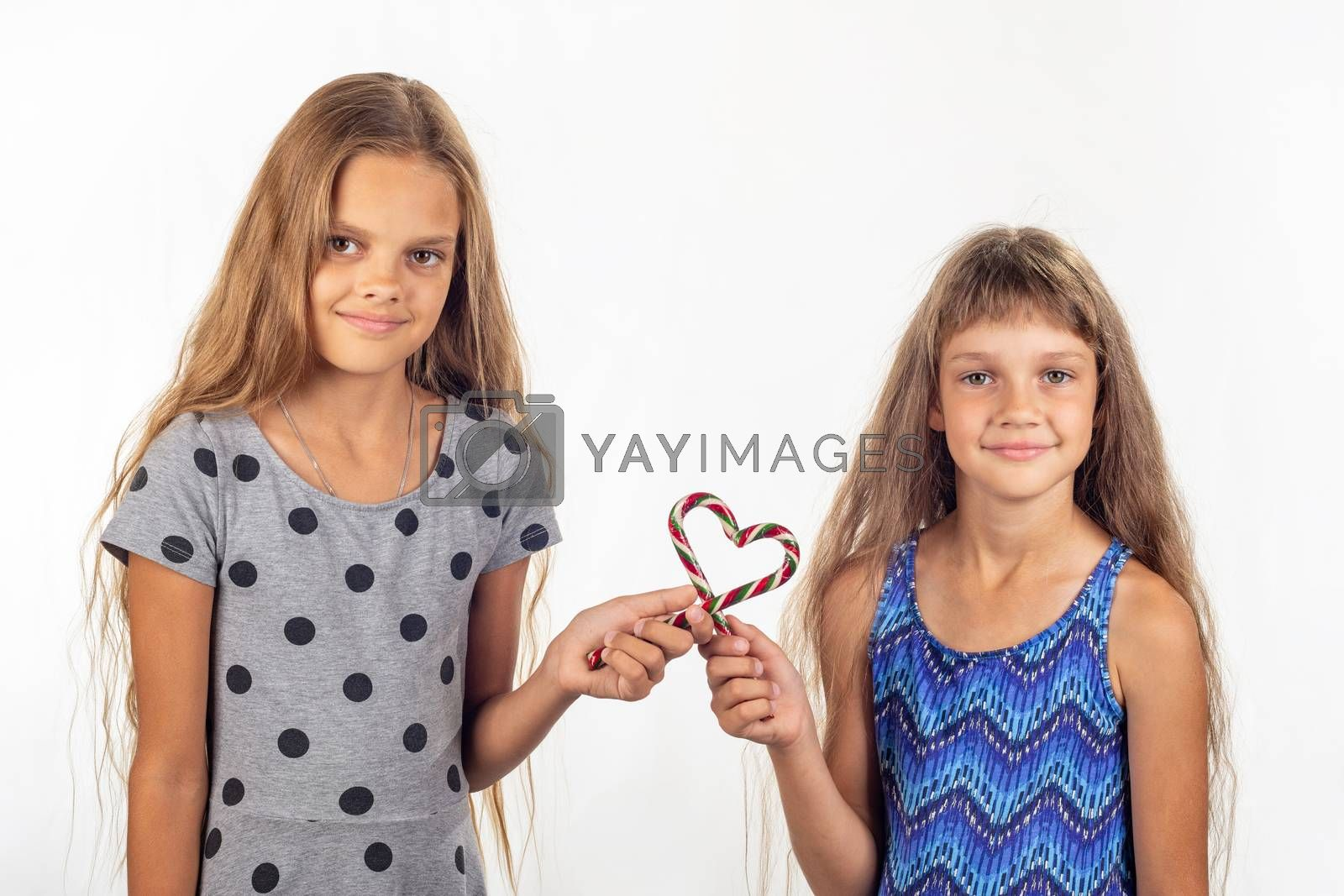 Two girls made a heart out of two lollipops and look into the frame by Madhourse