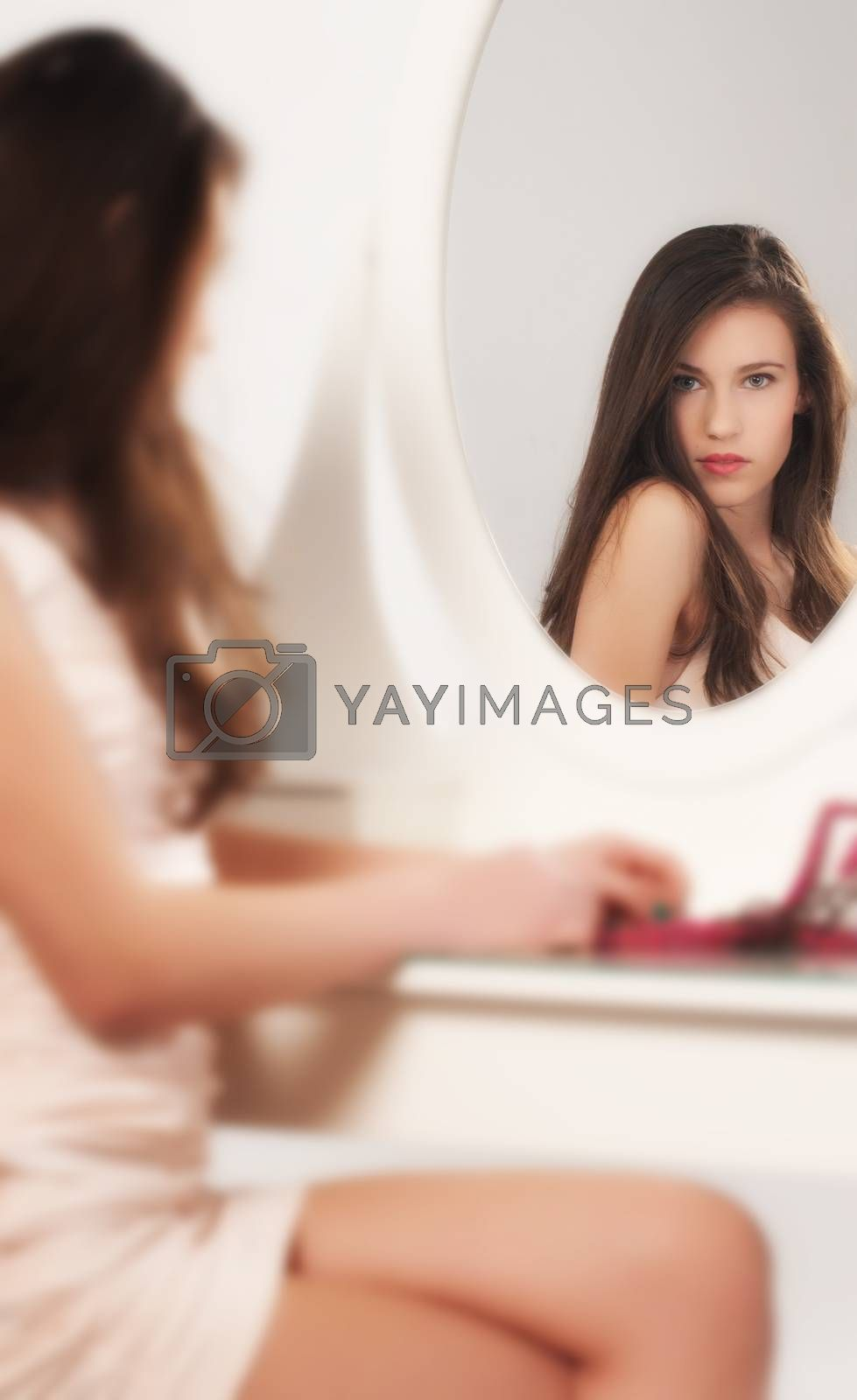 Brunette girl relaxing, preparing for make-up, looking in the mirror.