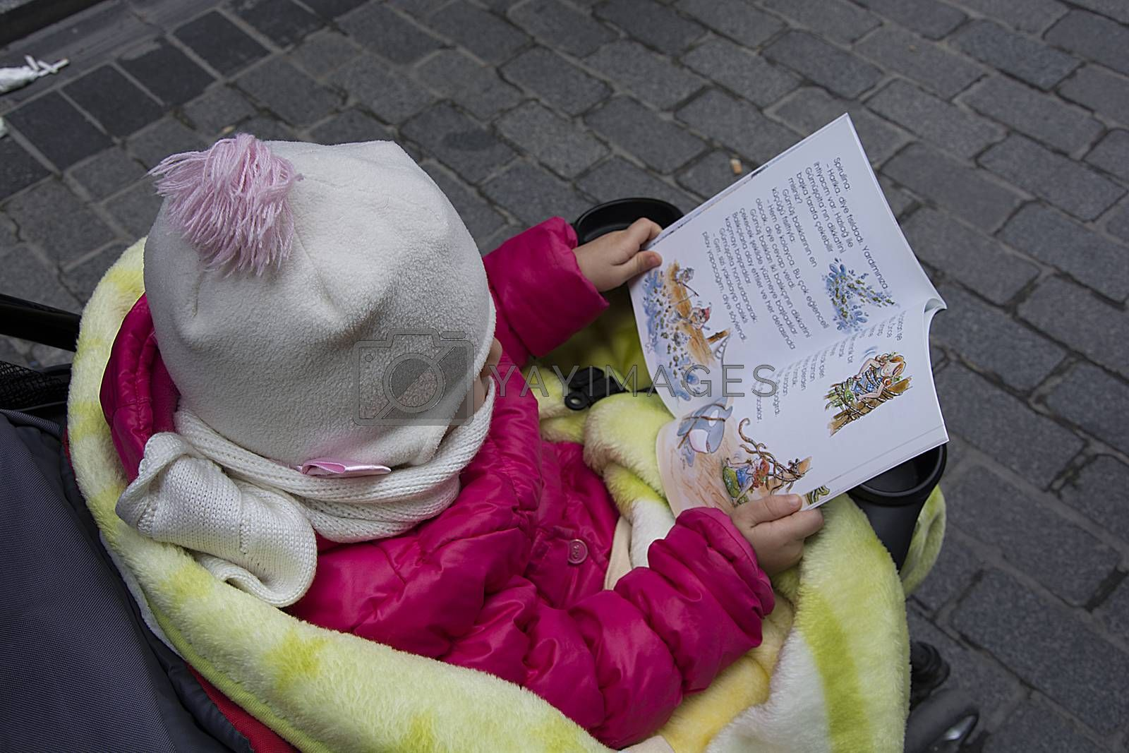 The child is reading the book by Nursel
