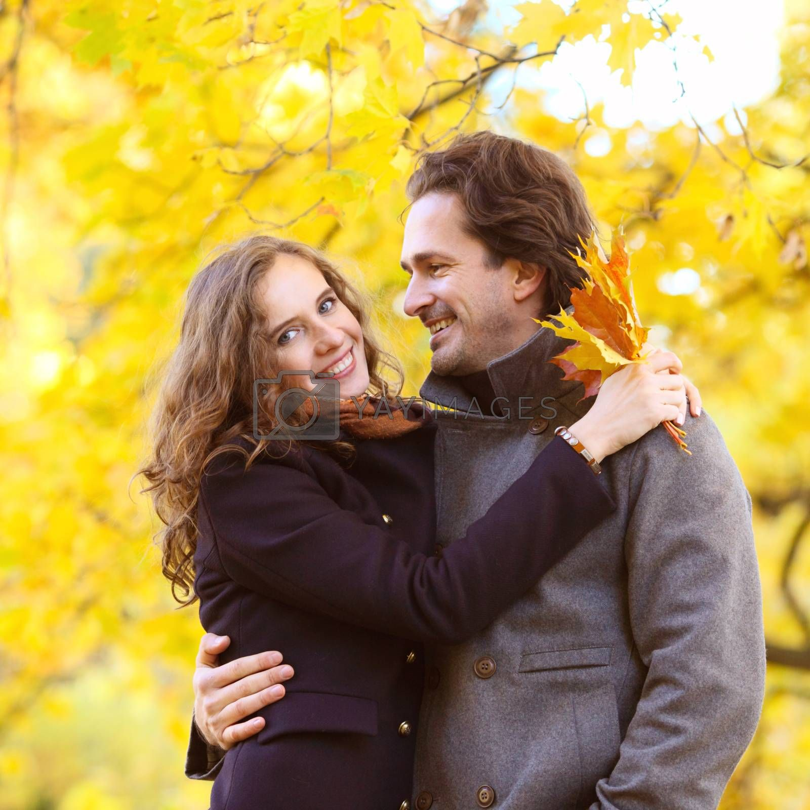 love, relationship, family and people concept - couple with maple leaves hug in autumn park