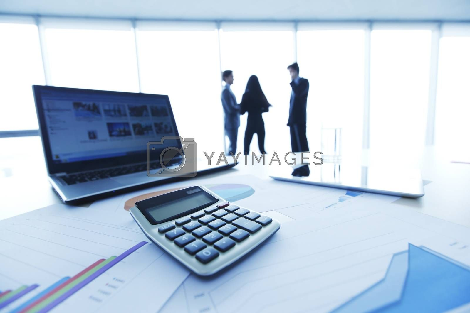 Financial reports, calculator and laptop on table in office