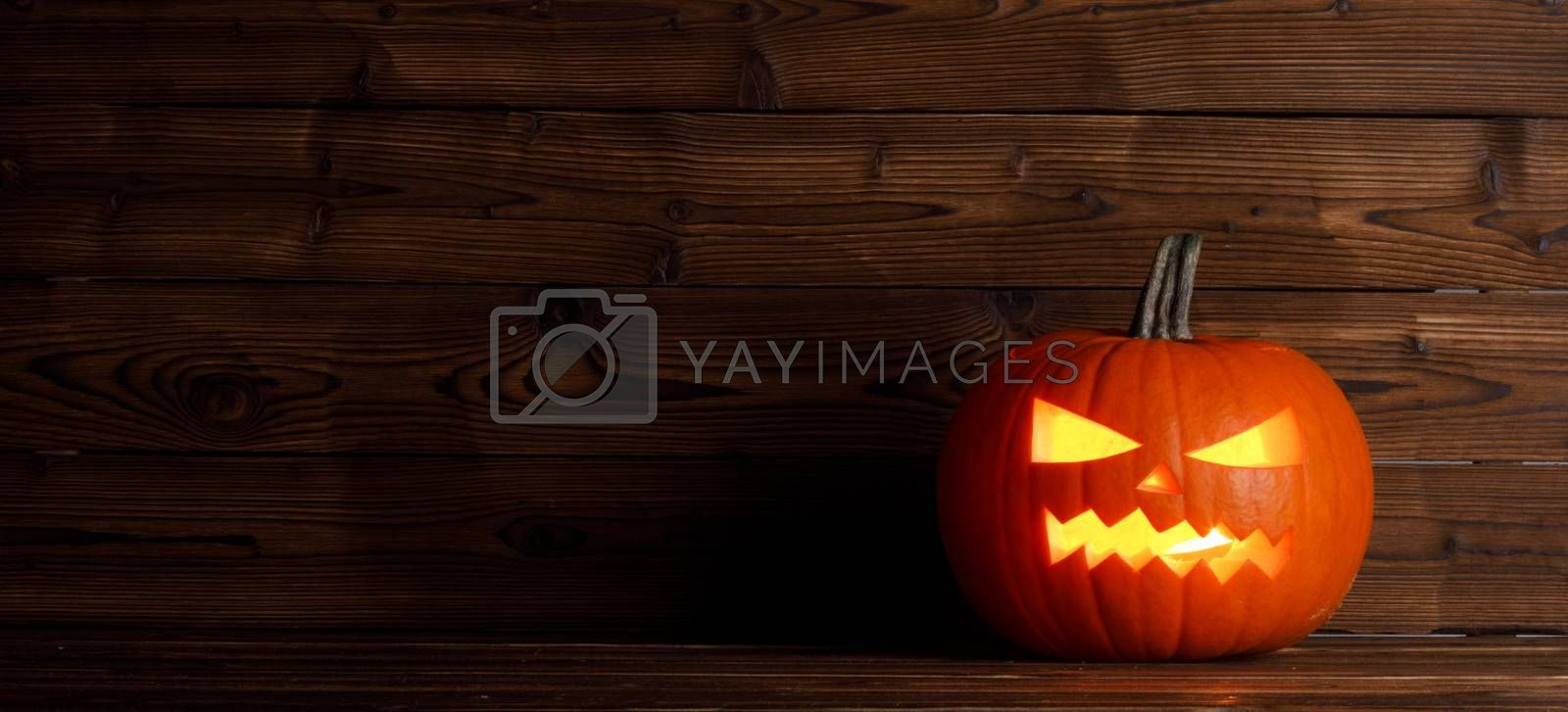 Halloween pumpkin head jack o lantern with candle inside on wooden background