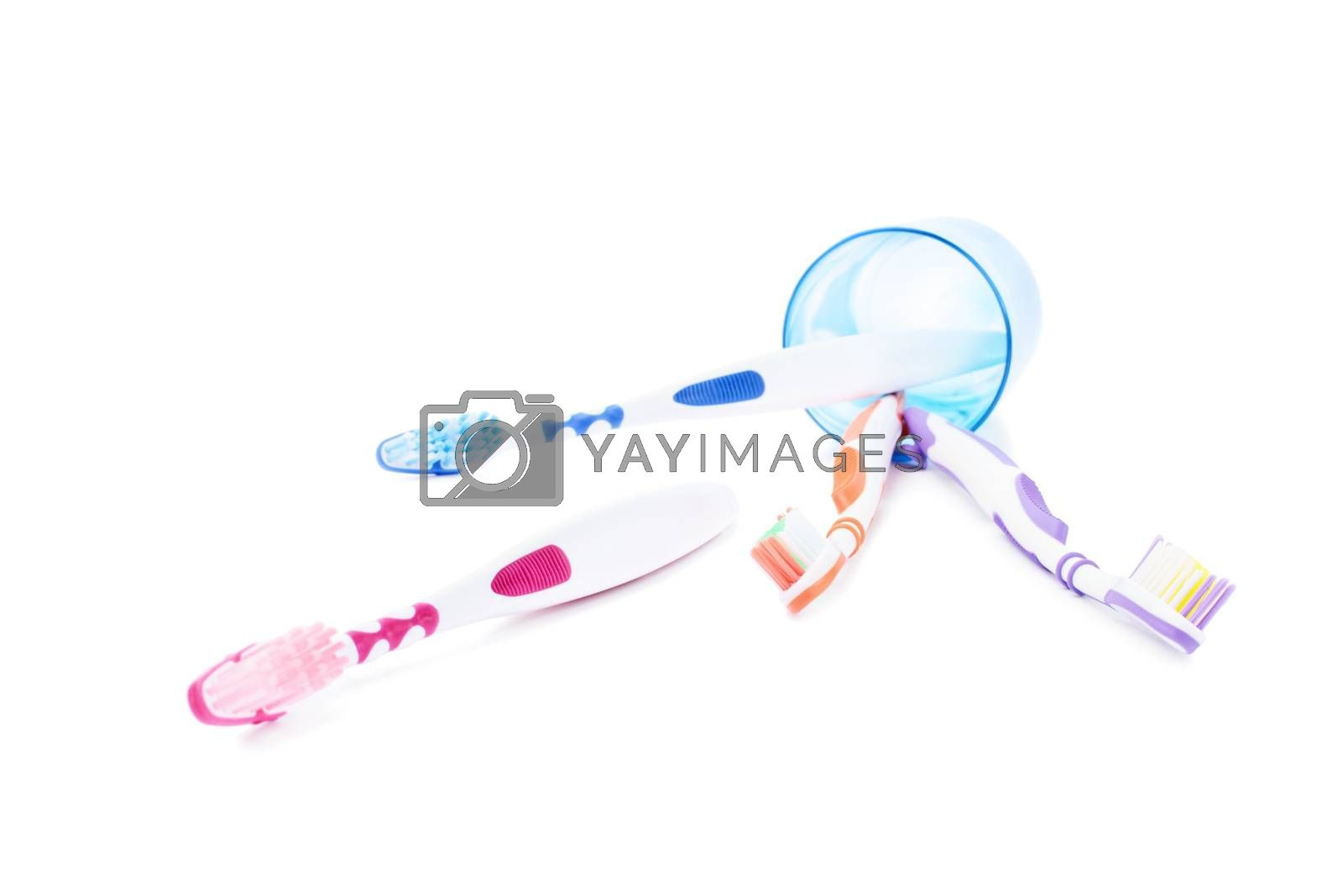 Fallen toothbrush cup holder with scattered toothbrushes, isolated on white background.