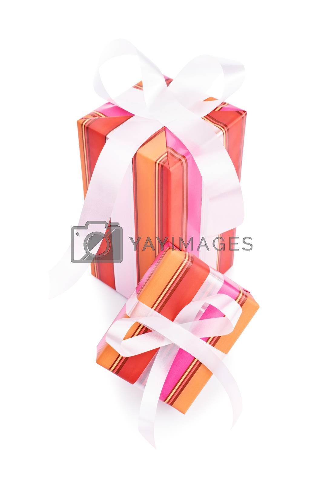 Two gifts wrapped in colorful wrapping paper with white ribbons, isolated on white background.
