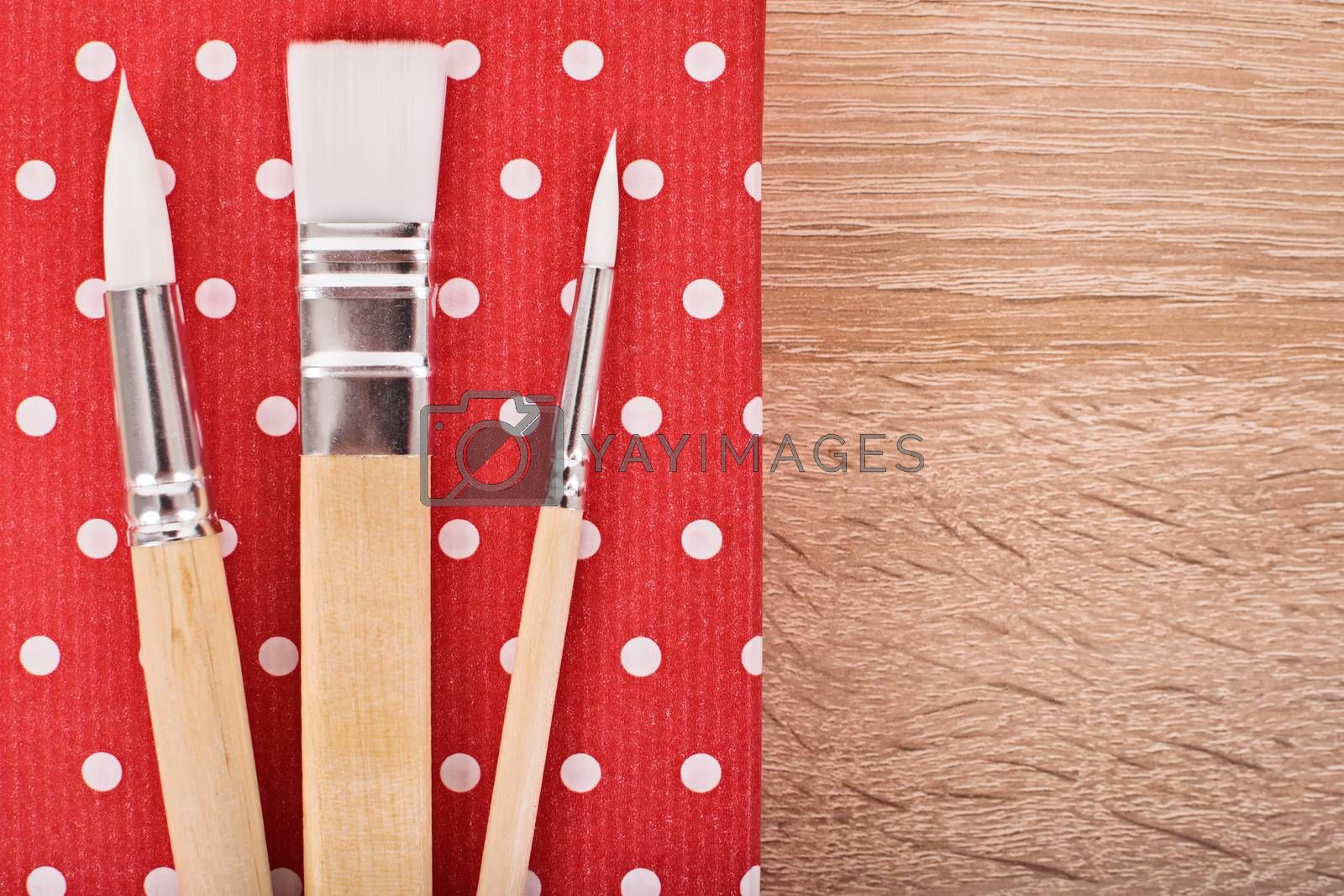 Close up shot of paint brushes on a wooden background.