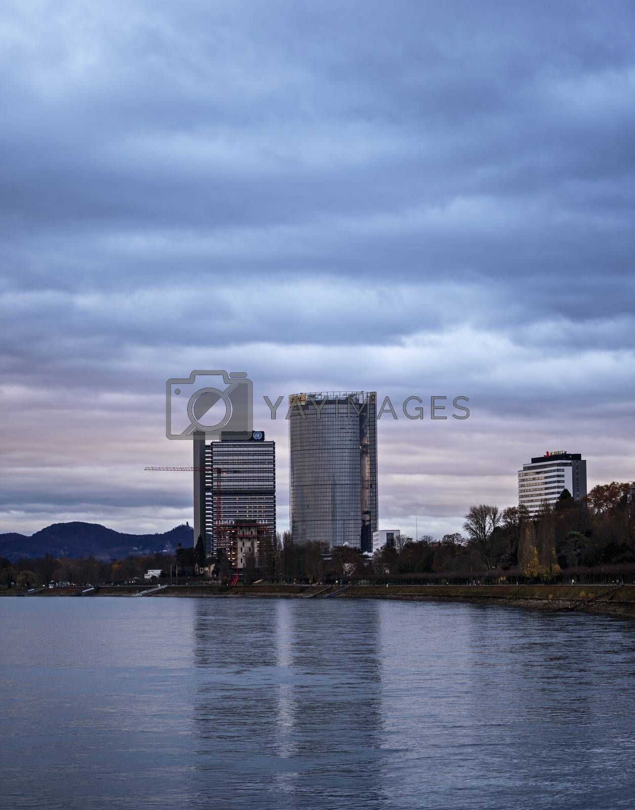 View of the Post Tower and United Nations building from the Rhine river at dusk.