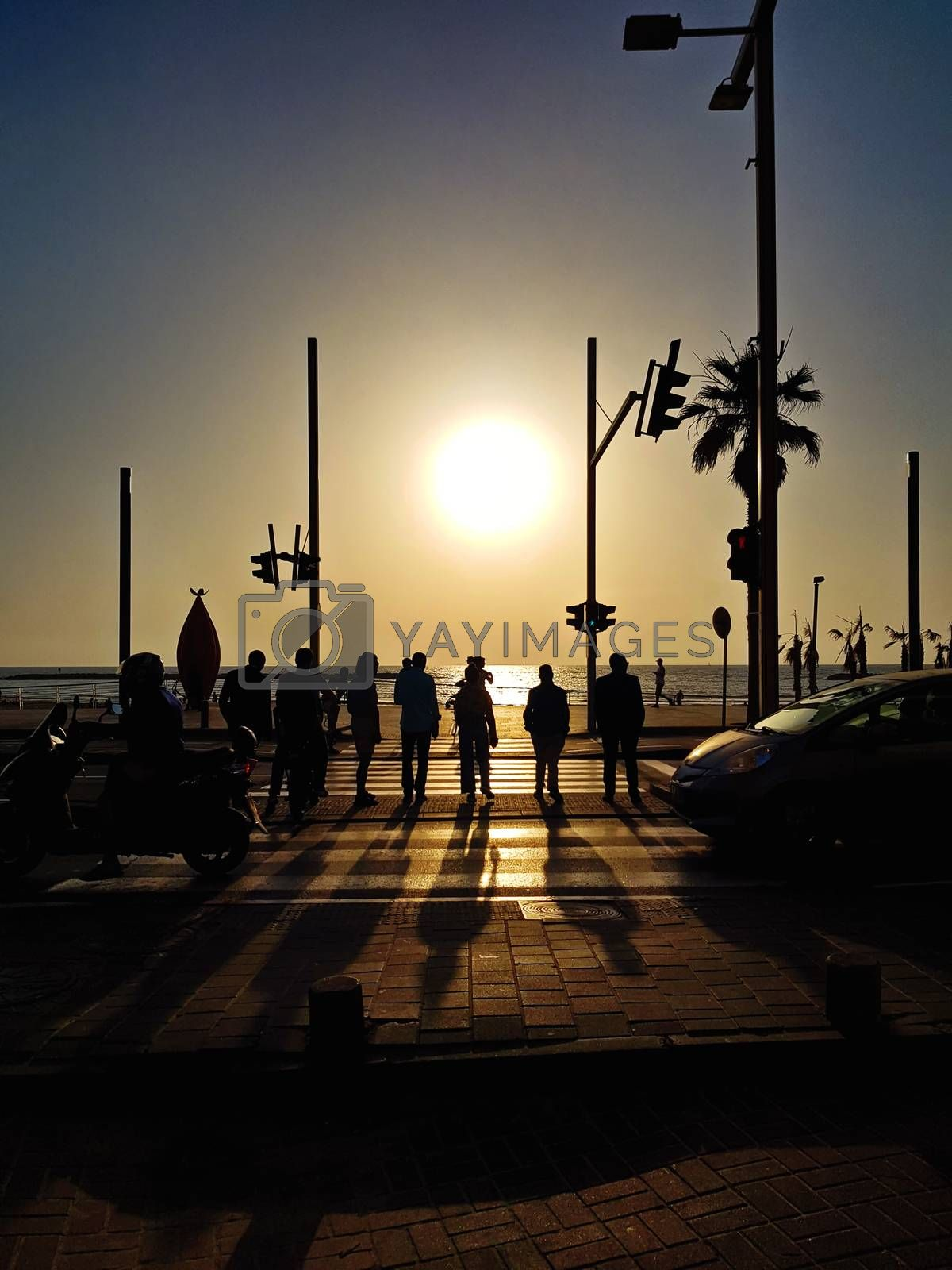 Silhouettes crossing street at sunset in Tel Aviv.