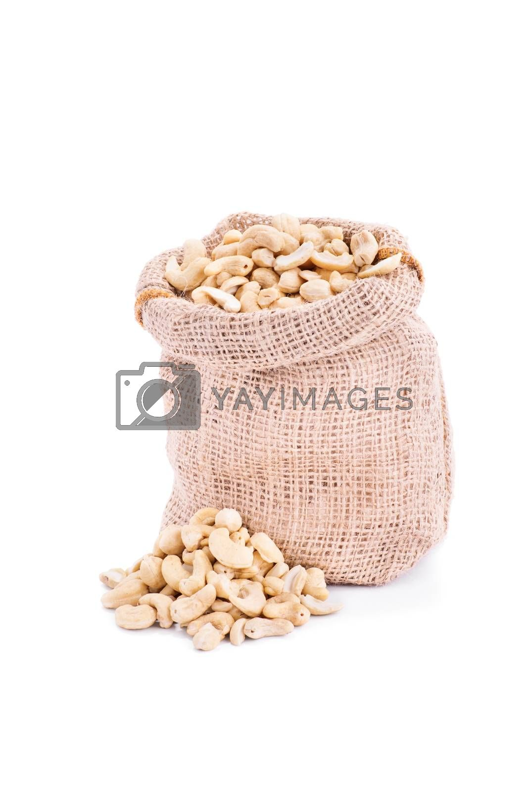 Small burlap sack of fresh cashews, isolated on white background.