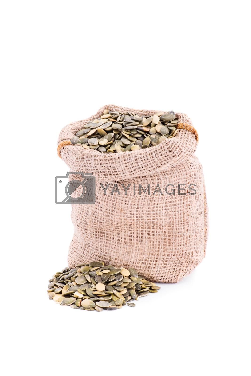 Small burlap sack of fresh pumpkin seeds, isolated on white background.
