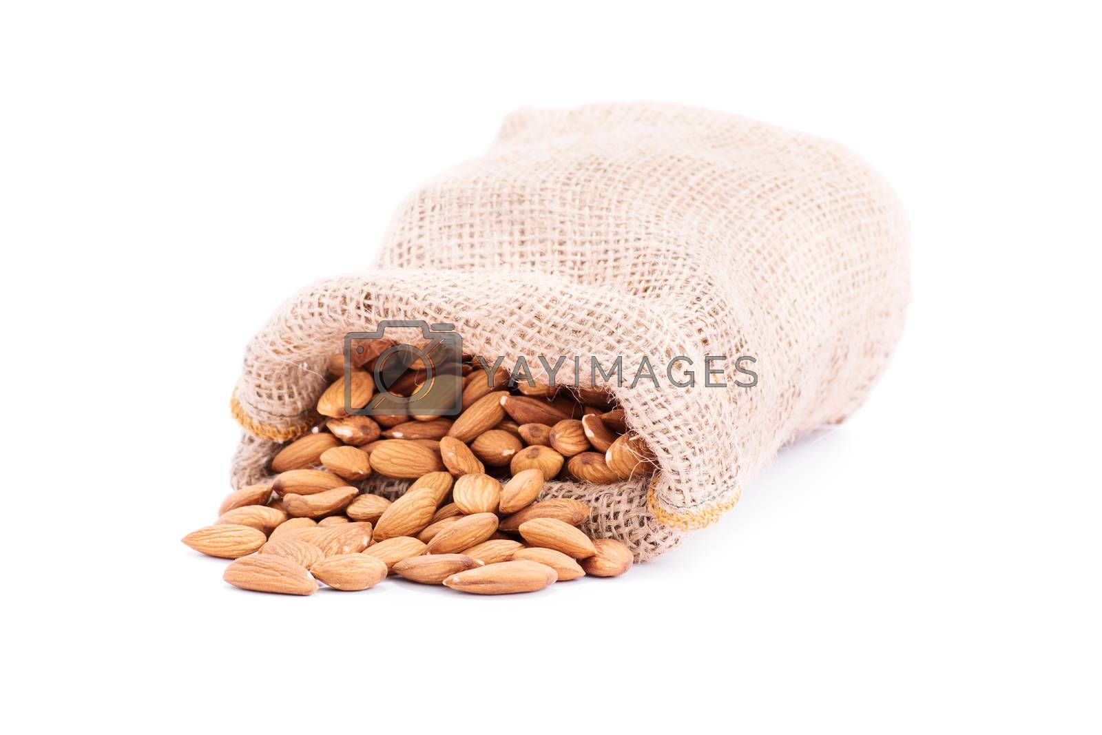 Close up shot of spilled burlap sack of almonds, isolated on white background.