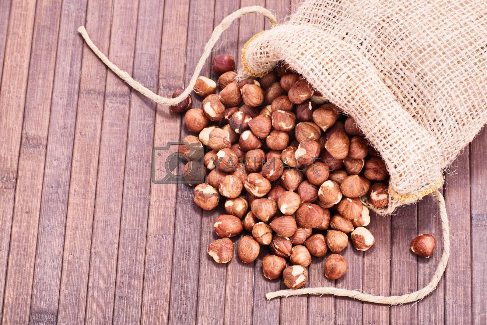 Close up shot of hazelnuts in a burlap sack spilled on wooden background.