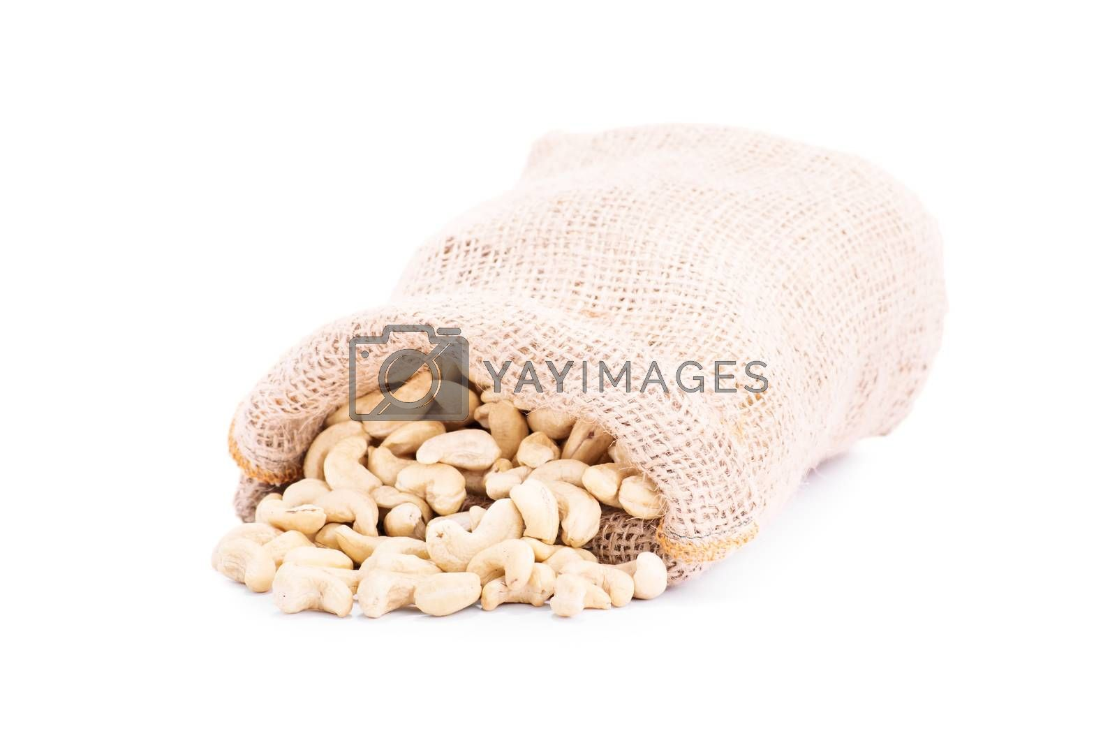 Spilled burlap sack of cashews, isolated on white background.